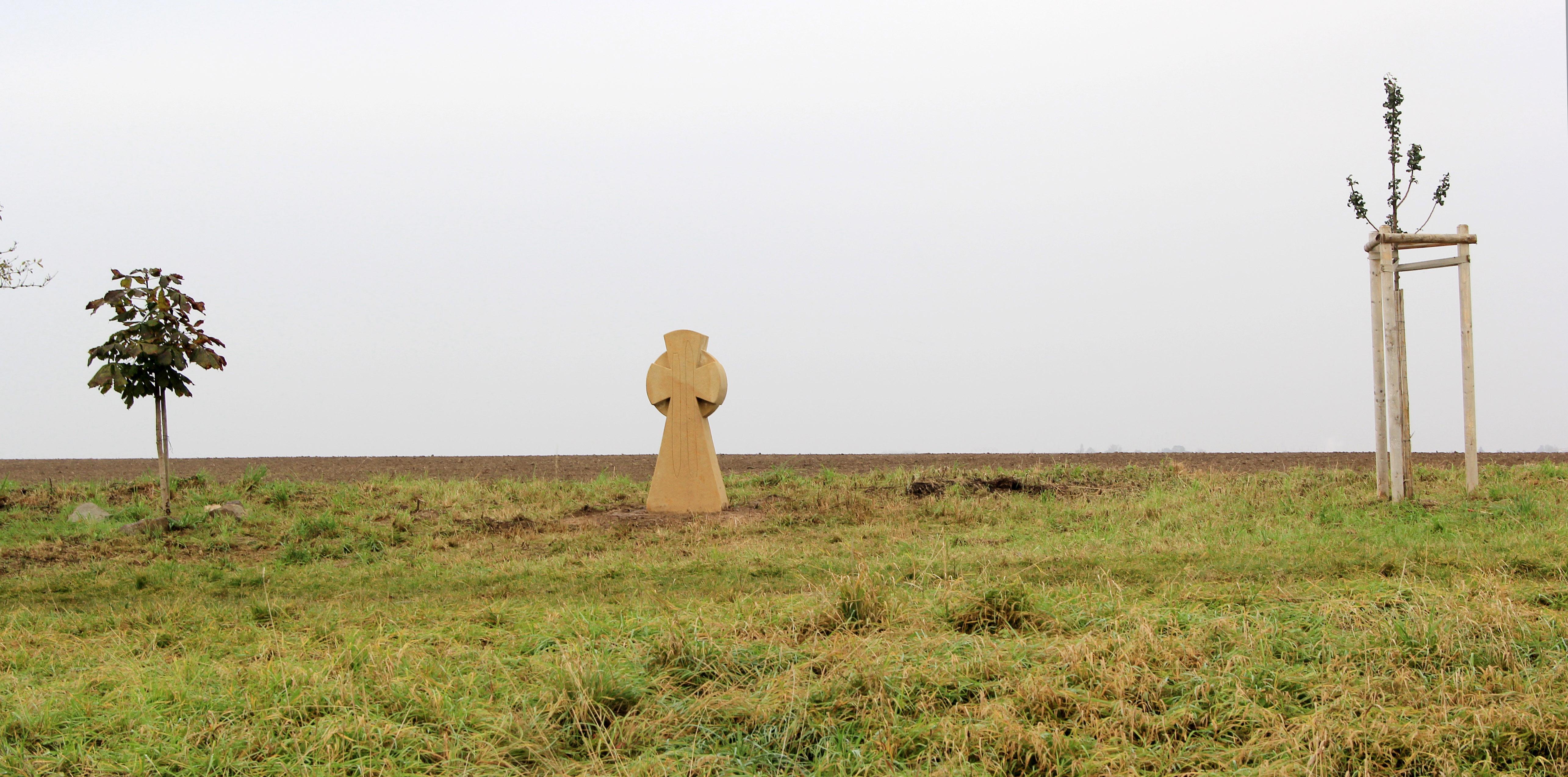 Auf Grünstreifen neben zwei jungen Bäumen steht ein Kreuz aus hellem Stein