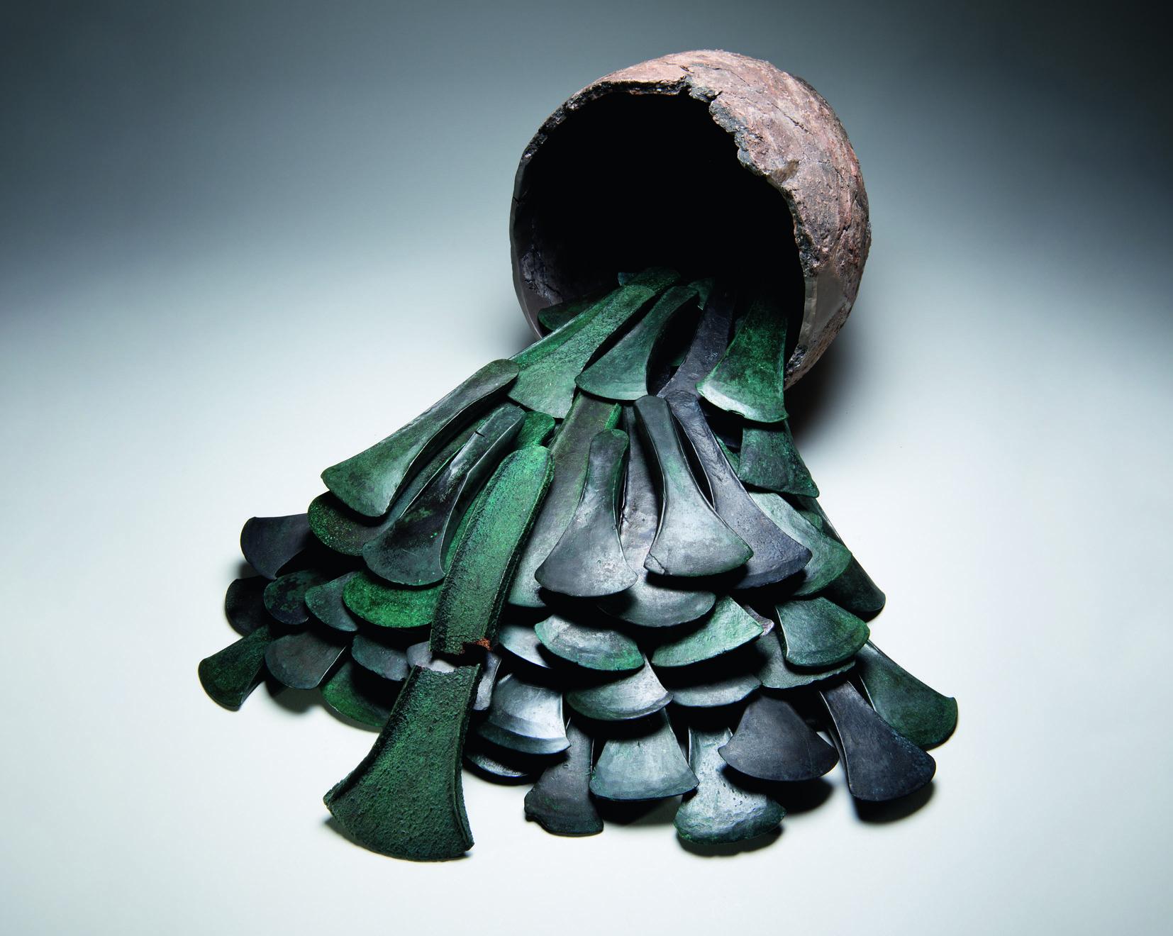 Viele dunkelgrünpatinierte Bronzebeile vor schmucklosem Keramikgefäß