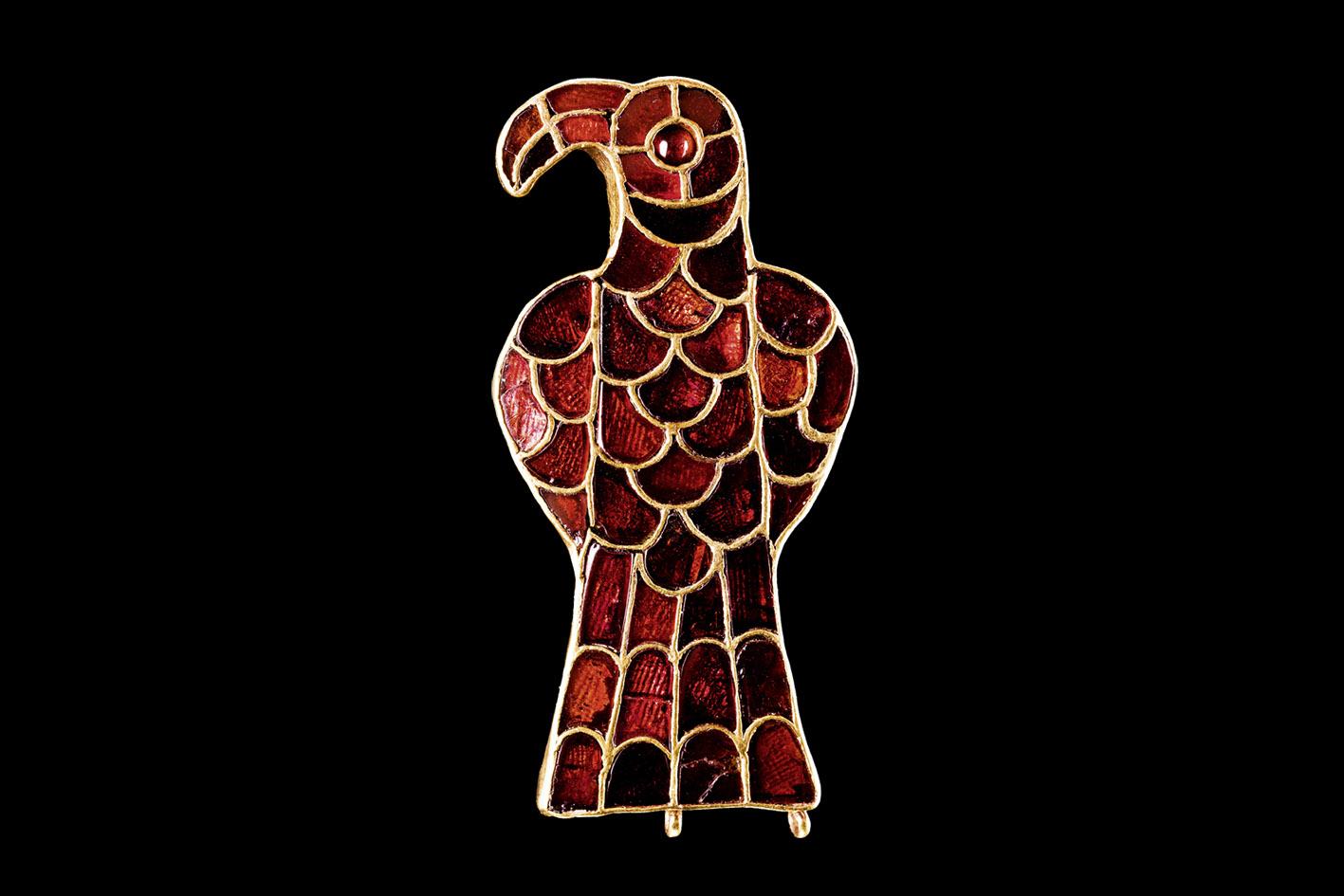 Goldenes Schmuckstück in Adlerform, mit vielen roten Schmucksteinen besetzt