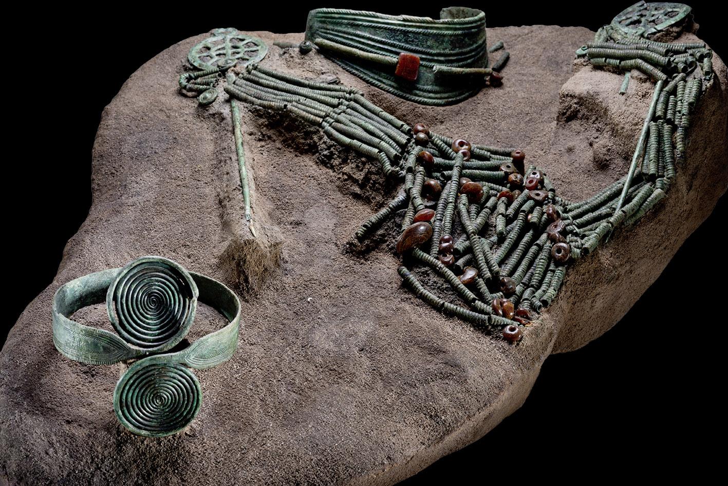 Hals- und Armschmuckgegenstände aus grün patinierter Bronze und braunen Perlen