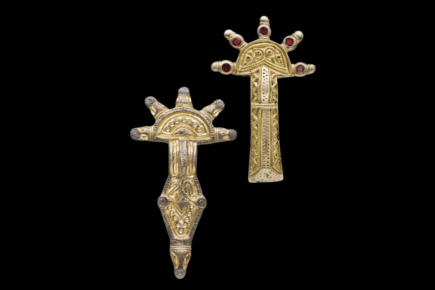 Zwei goldene Gewandspangen mit strahlenförmigen Köpfen und roten Schmucksteinen