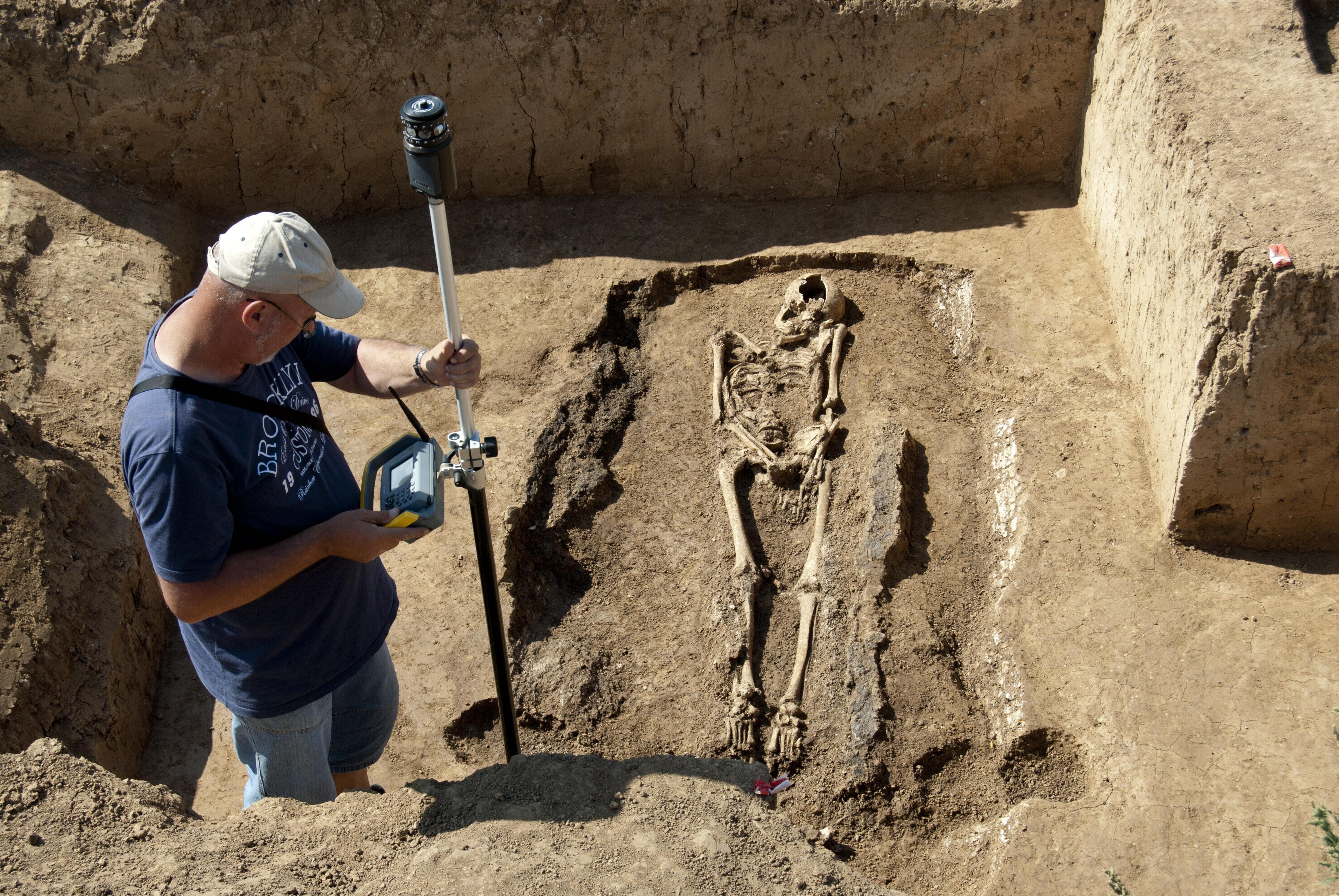 Grabungstechniker neben freigelegtem Skelett und vermisst Grab mit Messgerät