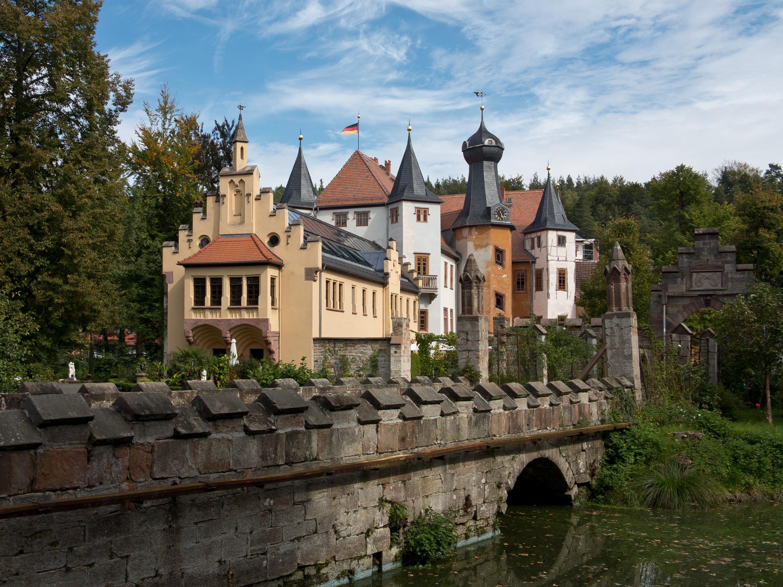 Unterschiedlich farbig verputztes Schloss mit Türmen und Toren umgeben von Wald