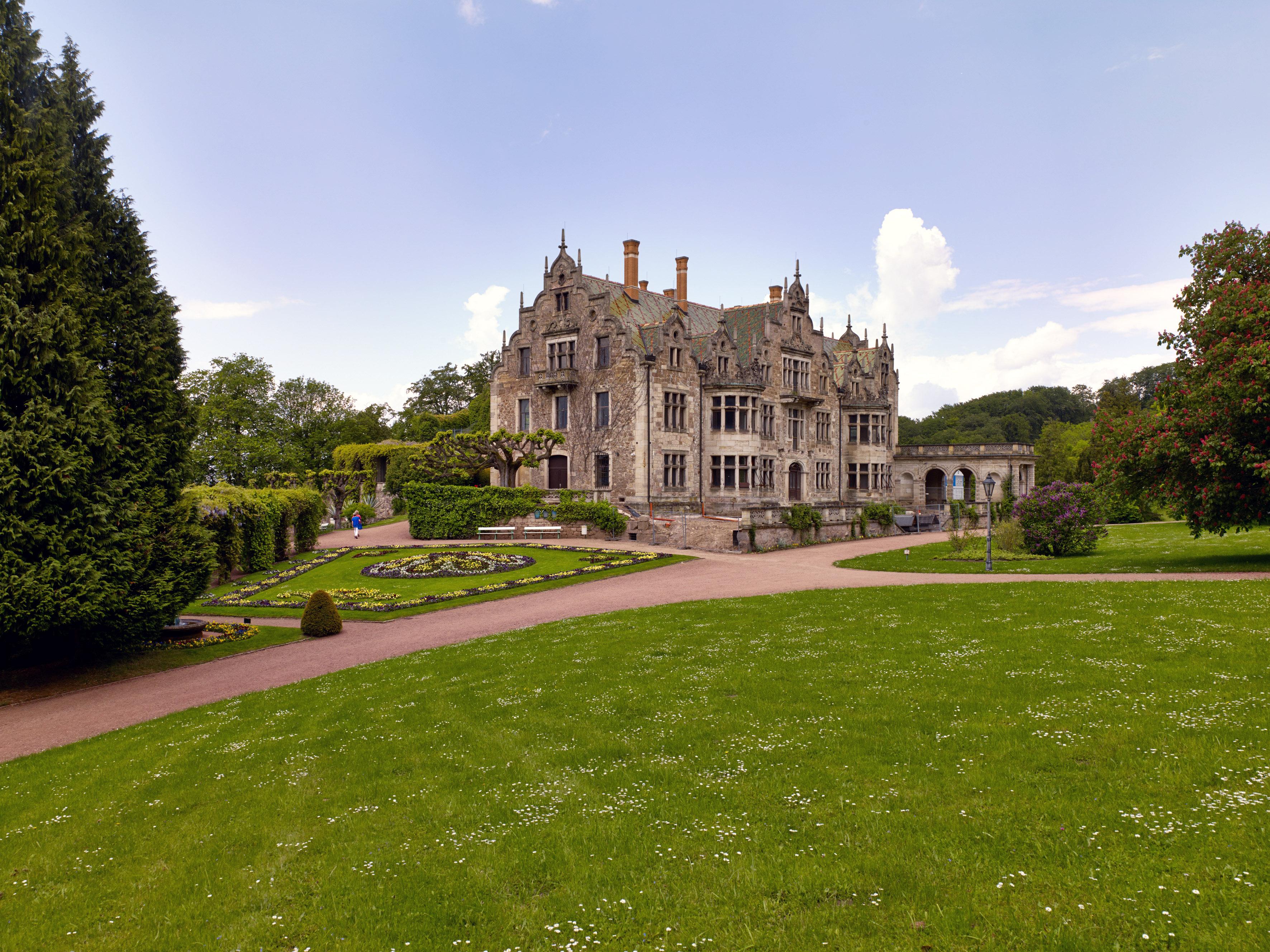 Barockes Schloss in einer Parkanlage mit Weg, Rasen und rundem Blumenbeet