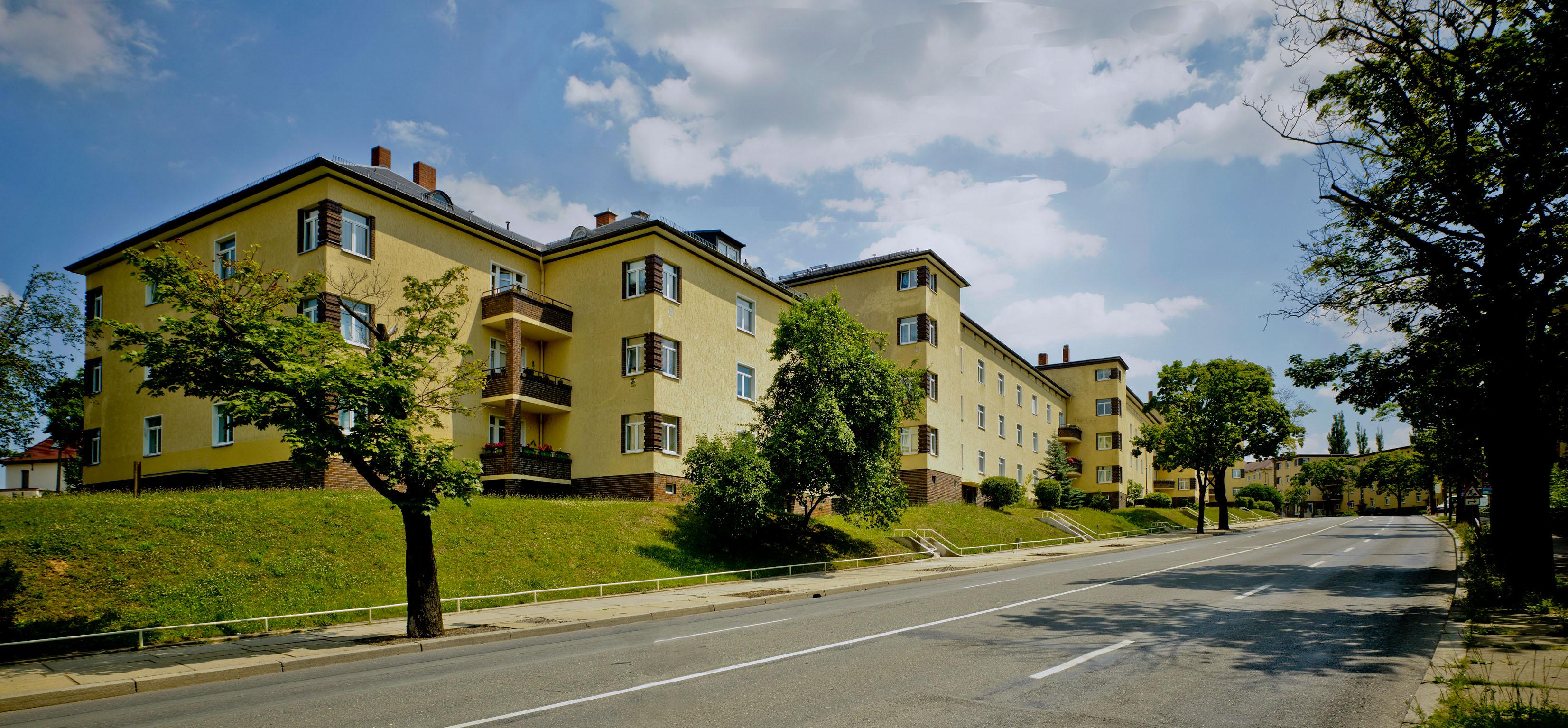 Straßenseitige Ansicht eines zweistöckigen gelbverputzten Wohnbolckes mit Balkonen und Fenstern über Eck