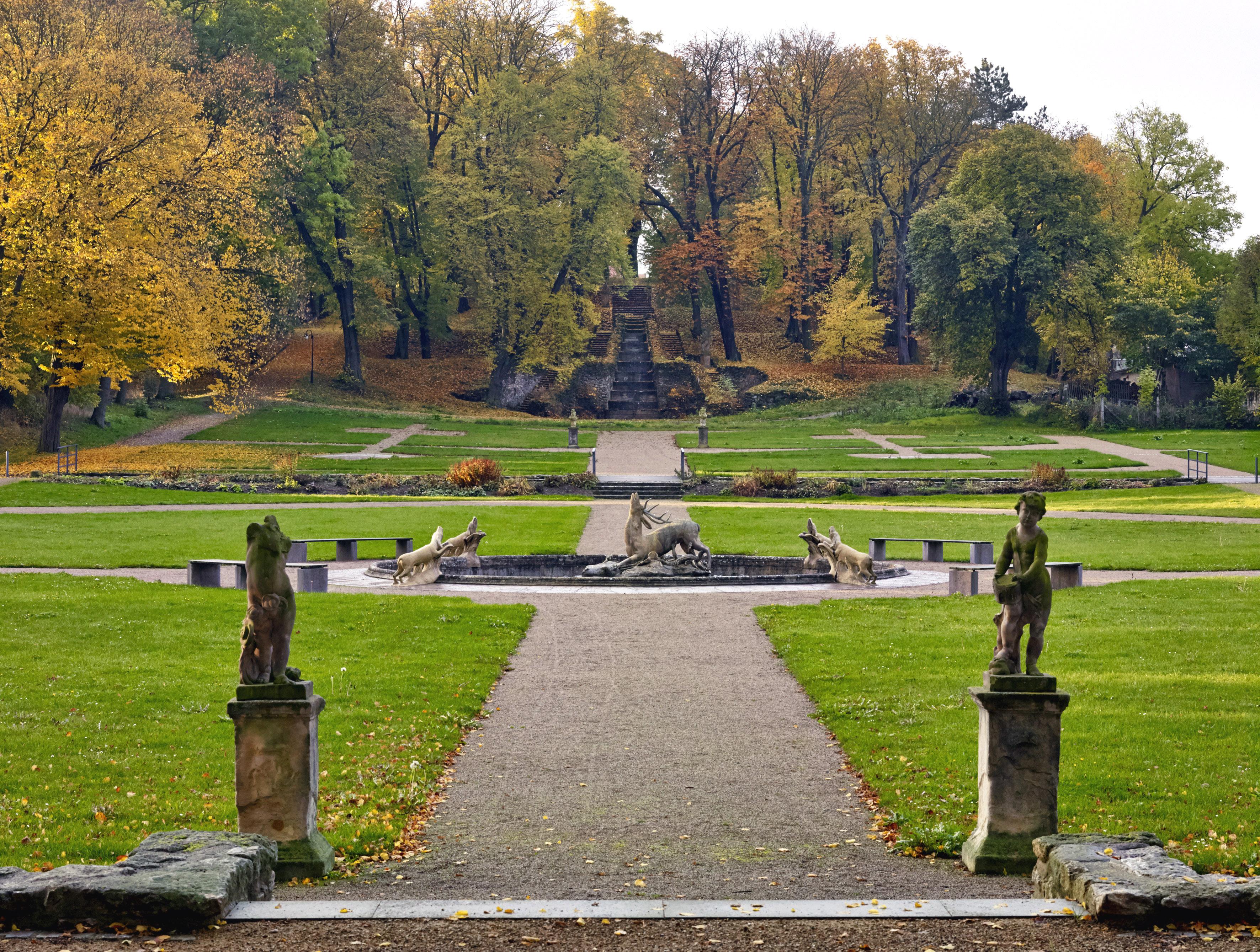 Herbstliche Parkanlage mit großer Kaskade, symetrischer Wegeführung und Putten im Vordergrund. Mittig ein Brunnenbecken mit einer Hirschskulptur und vier Jagdhunden herum.
