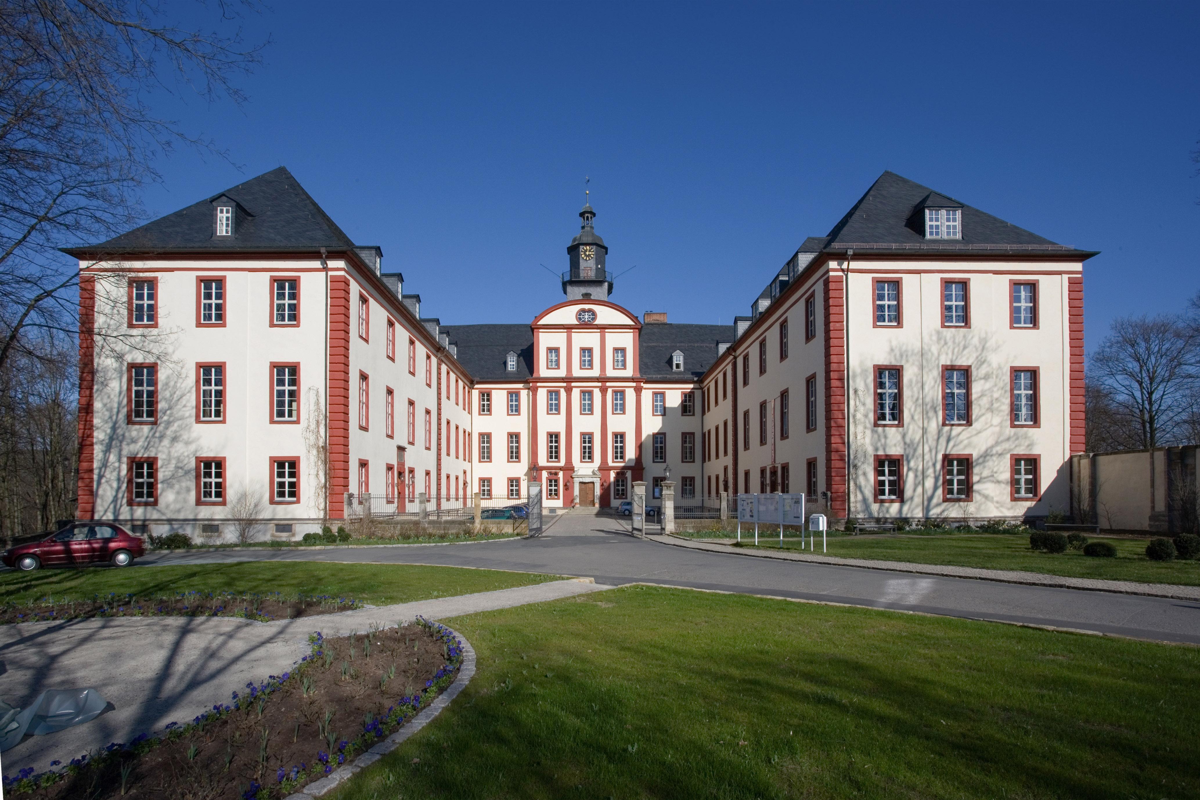 u-förmiges Schlossgebäude von vorn, Mittelteil mit Eingang, Turm und Turmuhr