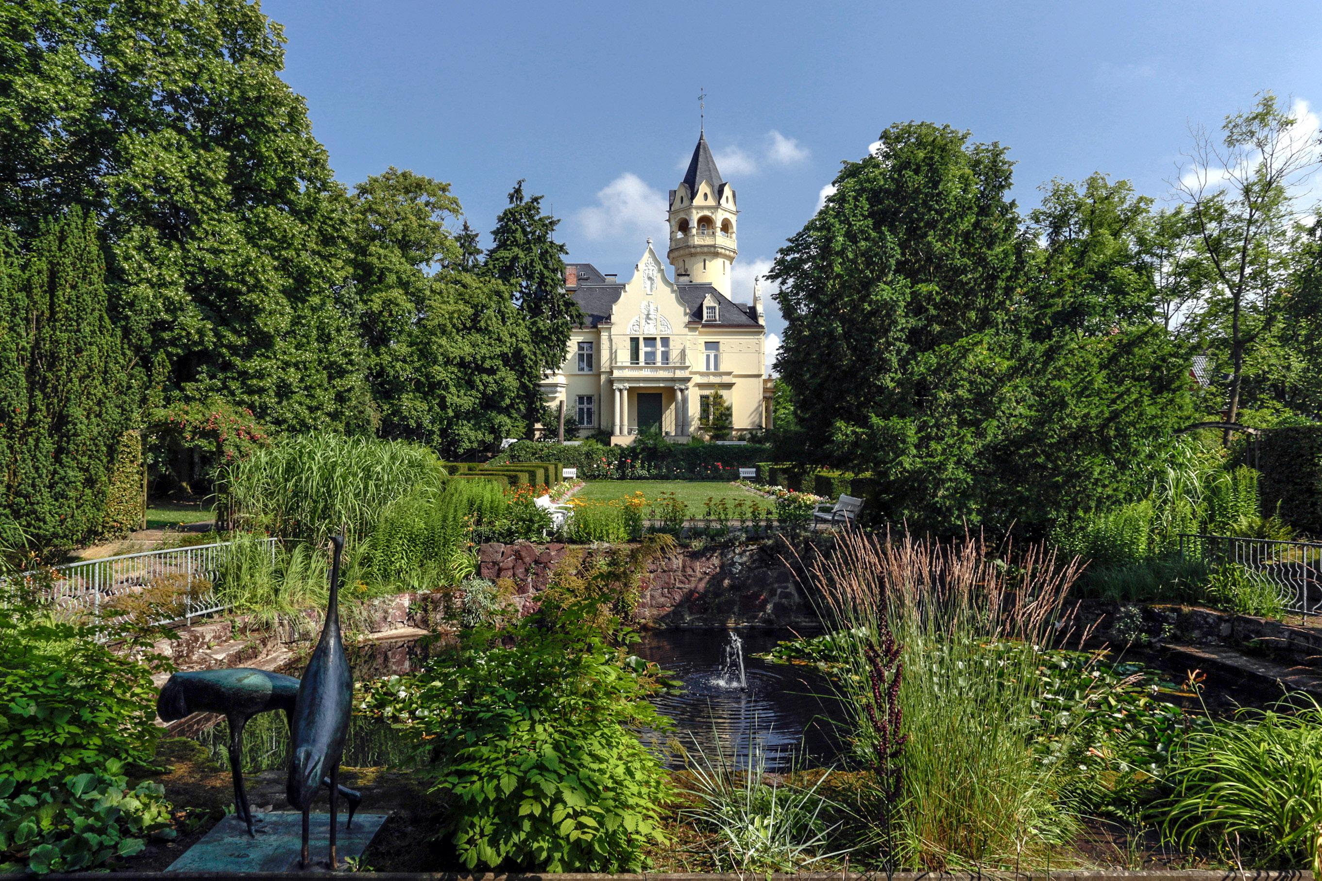 Jugenstil-Villa mit Turm und Balkon in einem Park mit Blumenrabatten und Teich