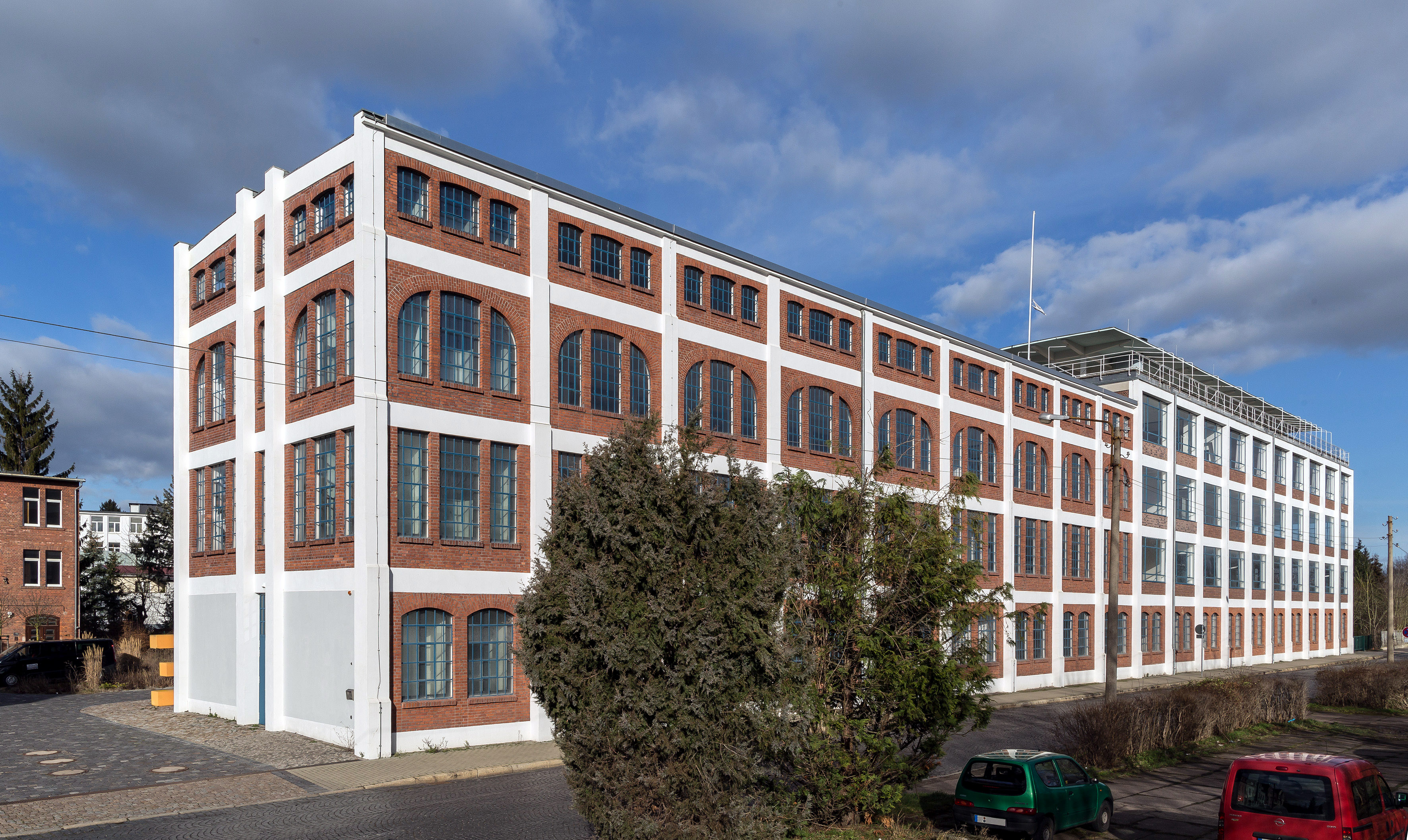 Viergeschossiger Industriebau, klar gegliederter mit großen rundbogigen Fenstern