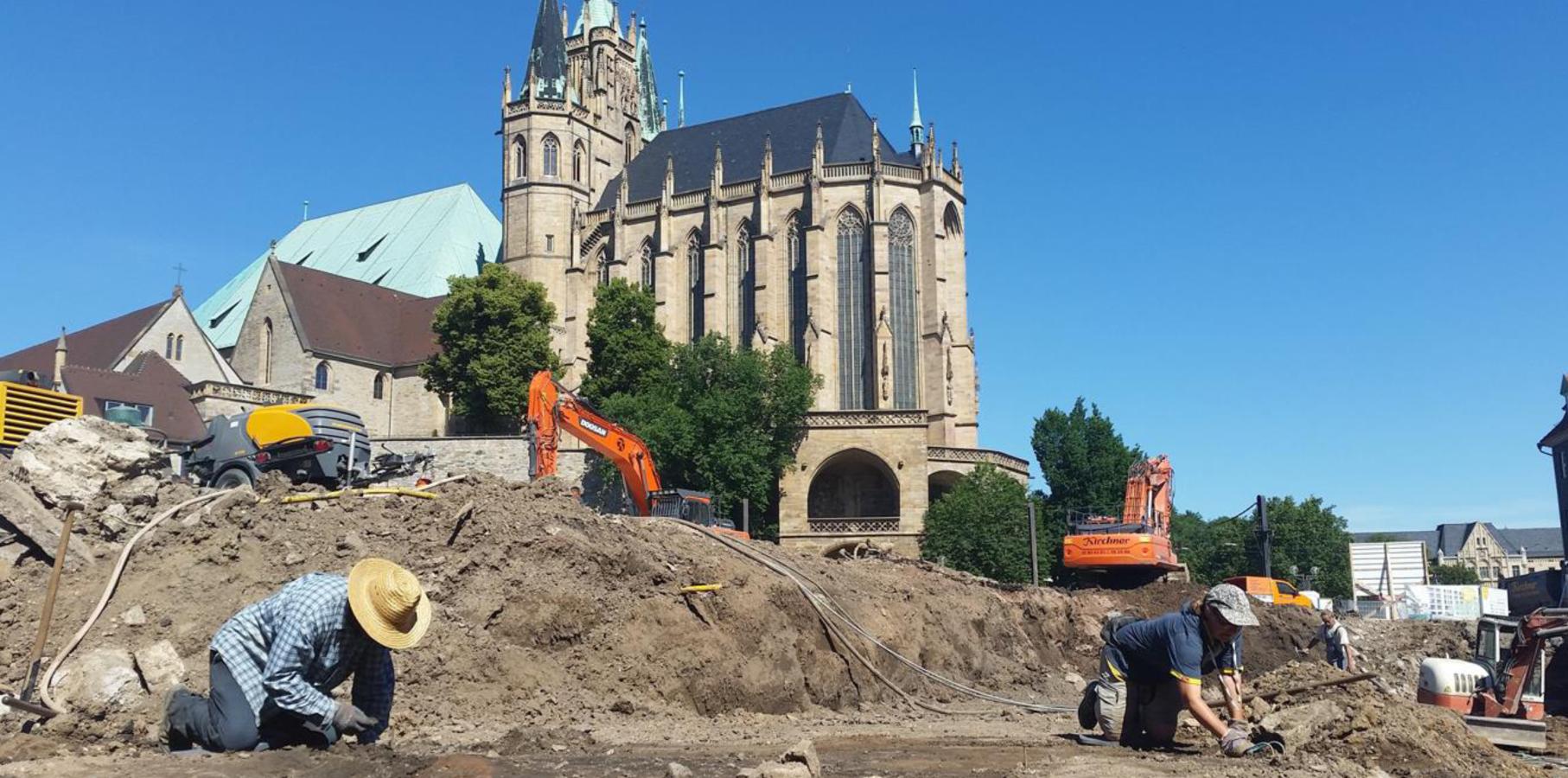Arbeitende Archäologen auf einer Ausgrabung, dahinter Bagger und Erfurter Dom