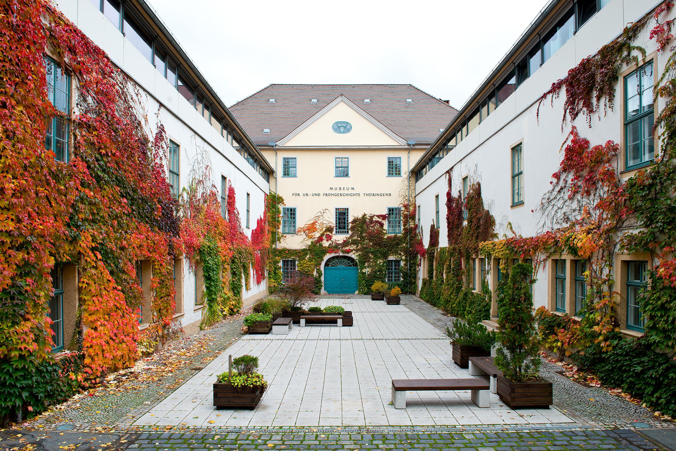 Blick in herbstlichen Museumshof auf Gebäude mit bunten Weinranken, davor Bänke