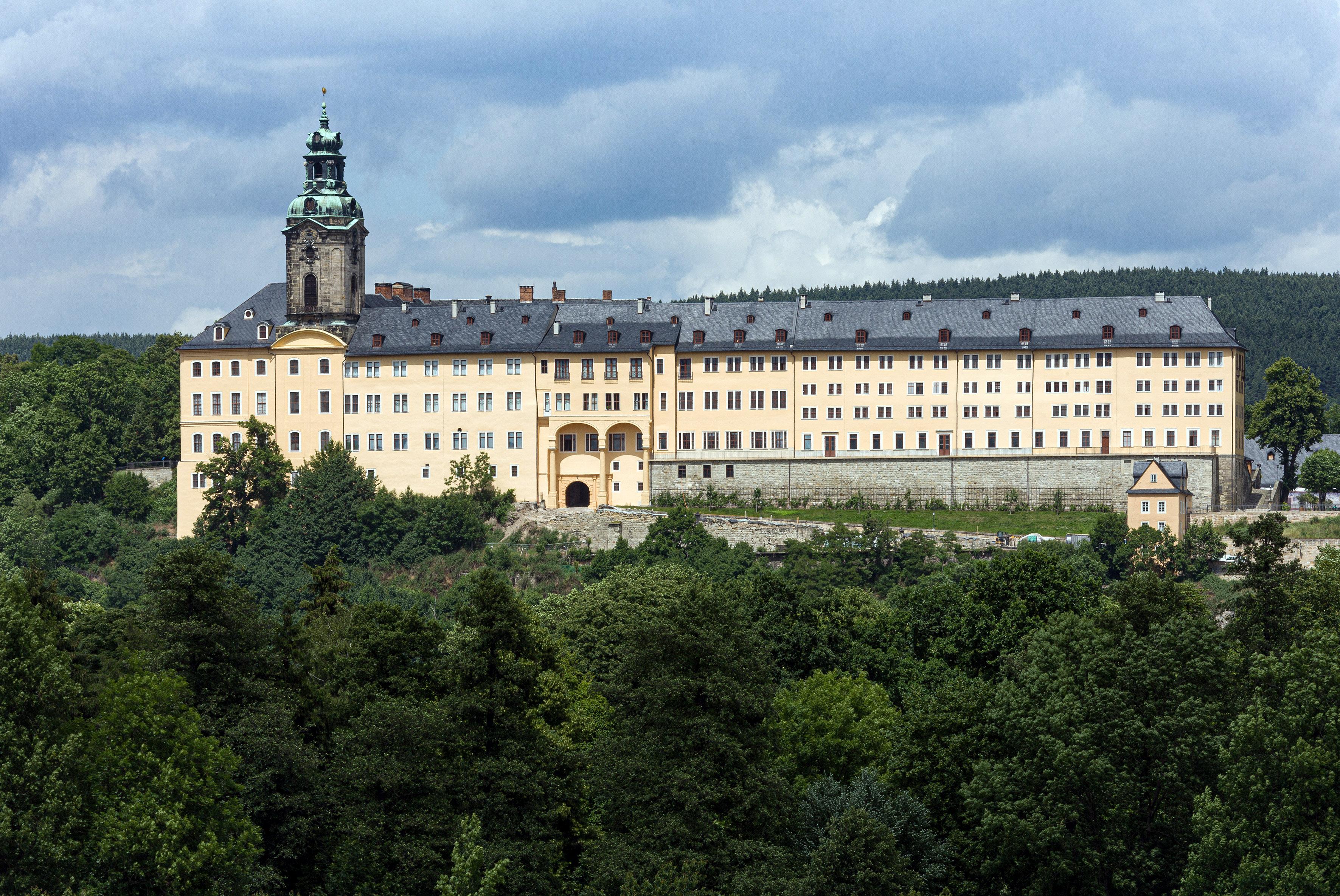 Heller, drei bis vierstöckiger Baukörper, links mit Turm, umgeben von Wald.