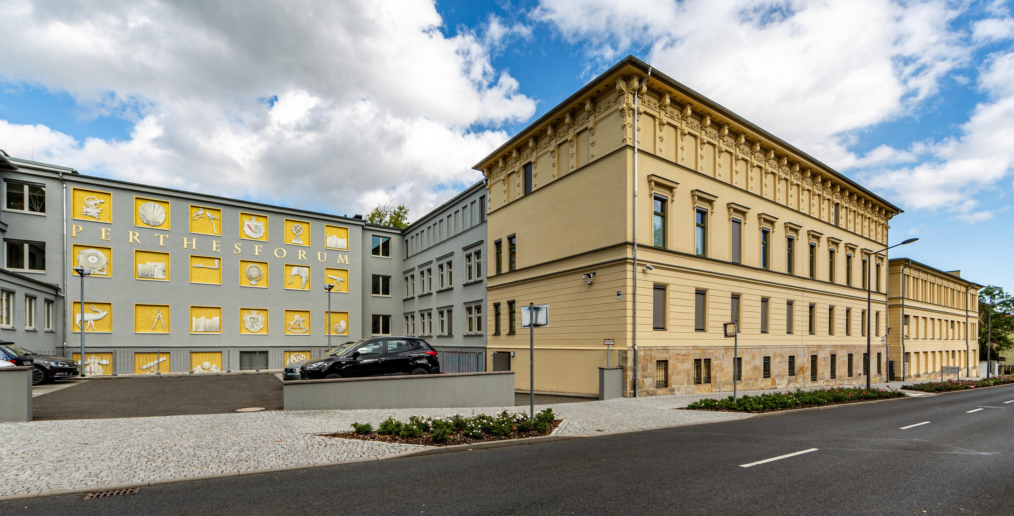 Dreistöckiges historisches Verlagsgebäude. Straßenseitig gelb verputzt mit Verzierungen. Links ein zurückgesetzter grau verputzer Flügel mit Schriftzug und gelb hinterlegten Ornamenten.