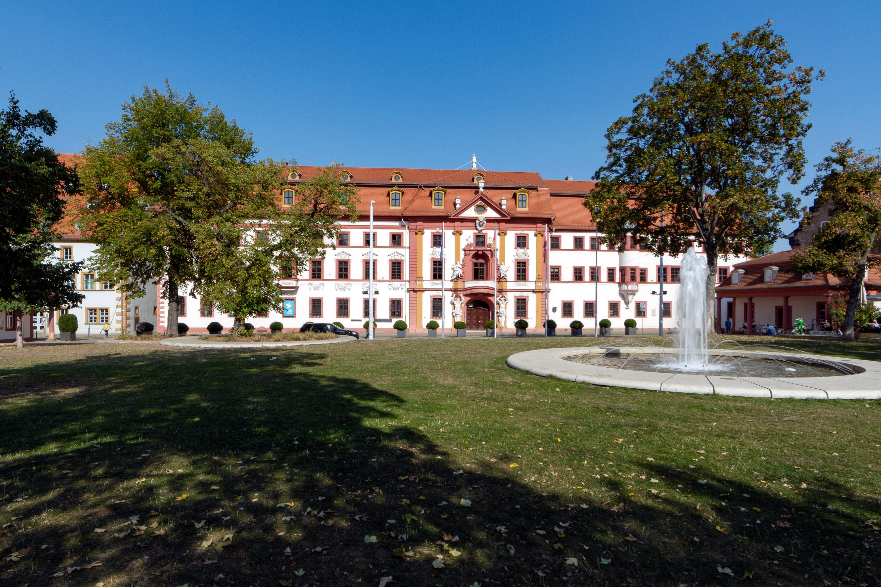 Gebäude, hell und rot verputzt, davor Springbrunnen, Wiese und Bäume.