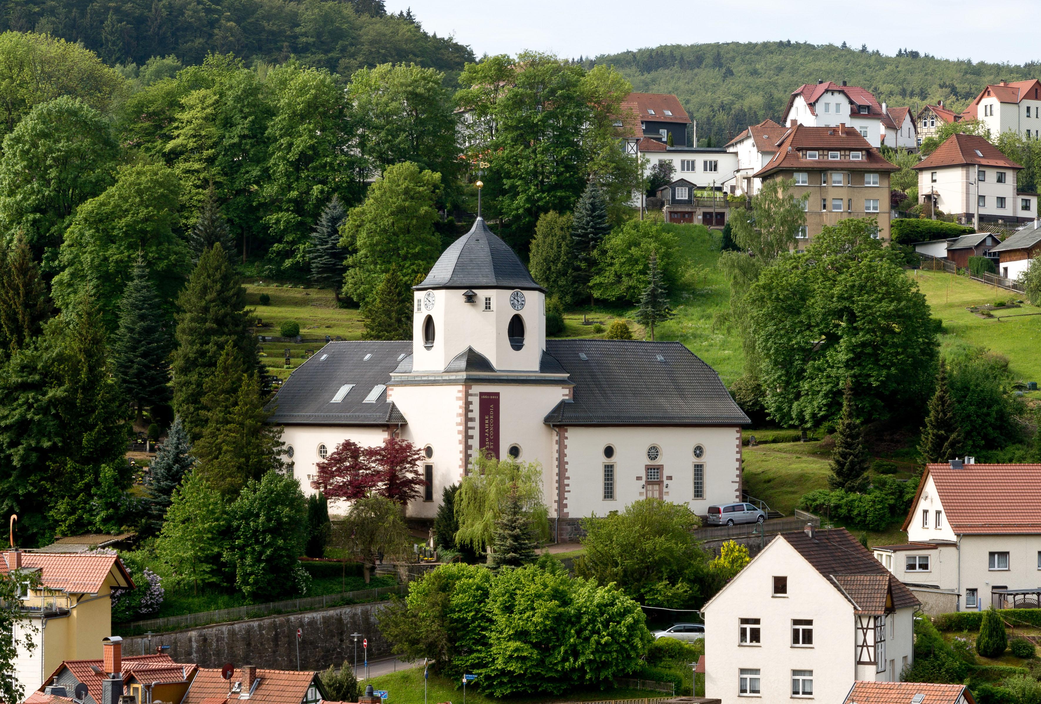 Zweischiffige Kirche mit niedrigem, breitem Turm. Umgeben von grünen Bäumen.