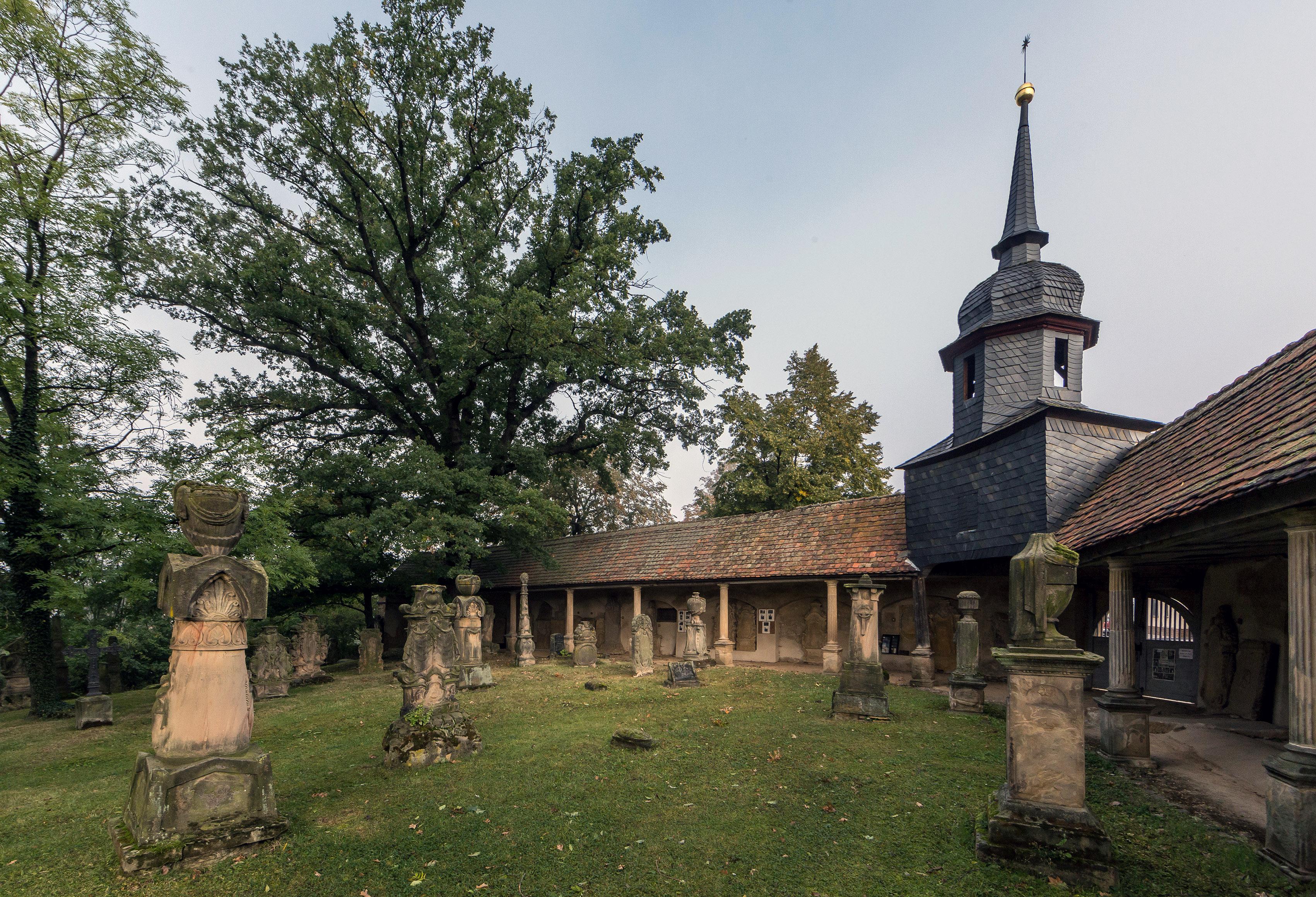 Friedhof mit Grabsteinen, Torturm und überdachtem Gang
