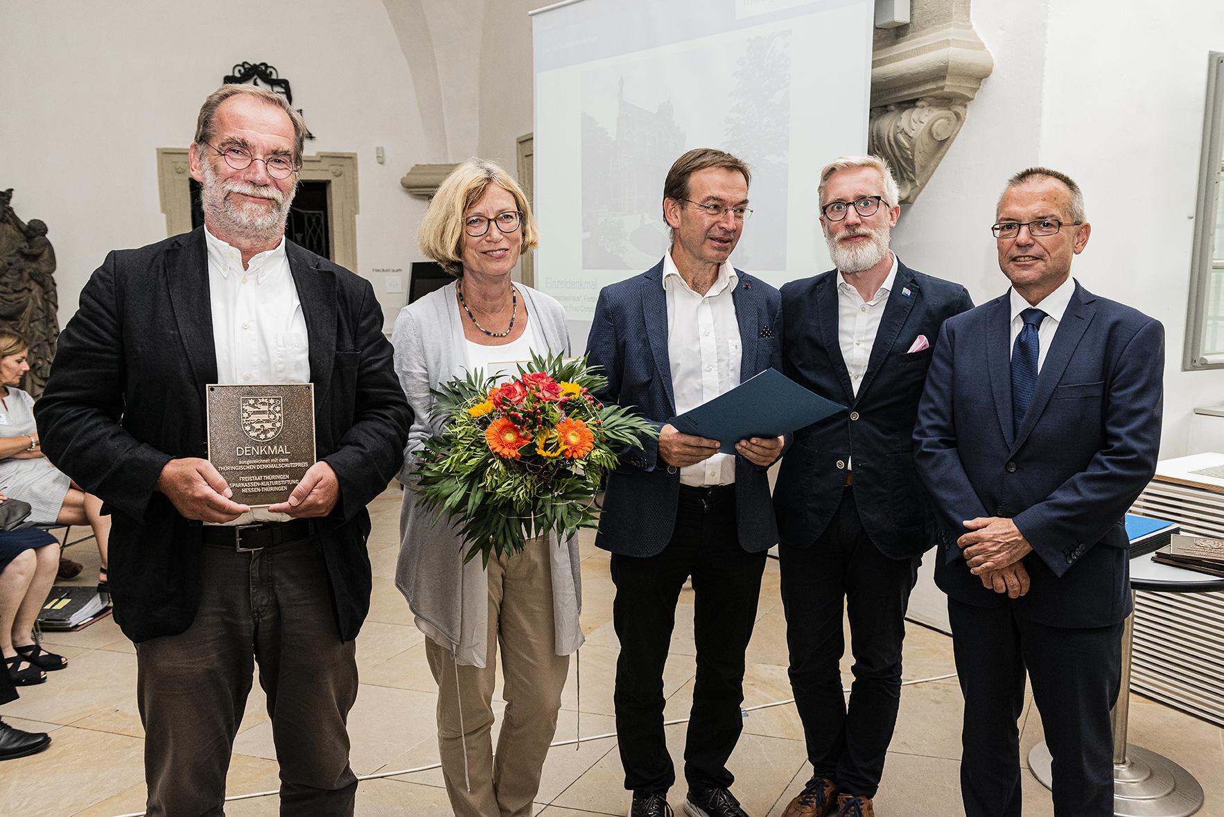 Fünf Personen bei Preisübergabe, mit Denkmalplakette, Blumenstrauß und Urkunde