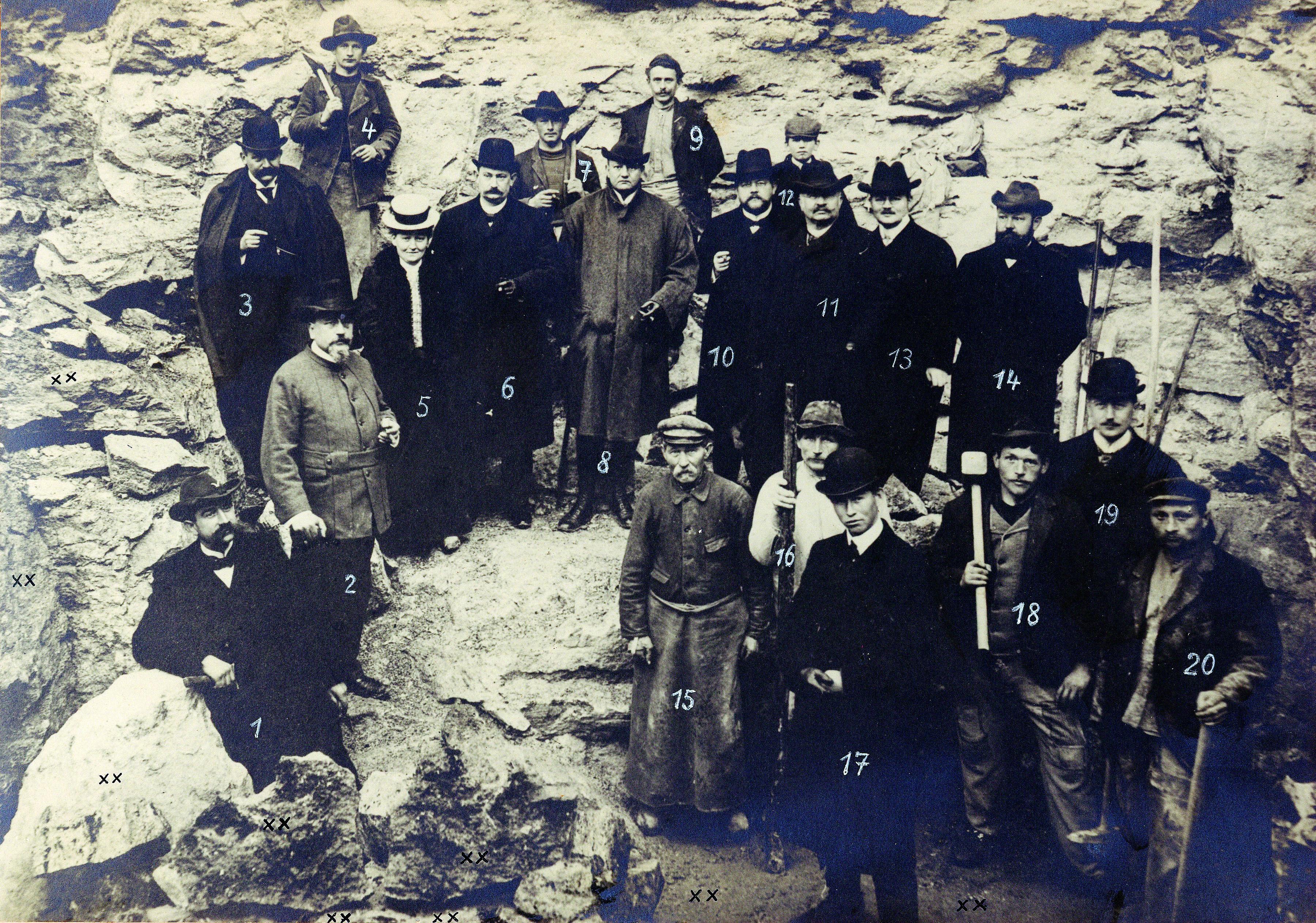 Historisches schwarz-weiß-Foto, Gruppenaufnahme von 20 Personen, stehend zwischen hellen Steinklüften