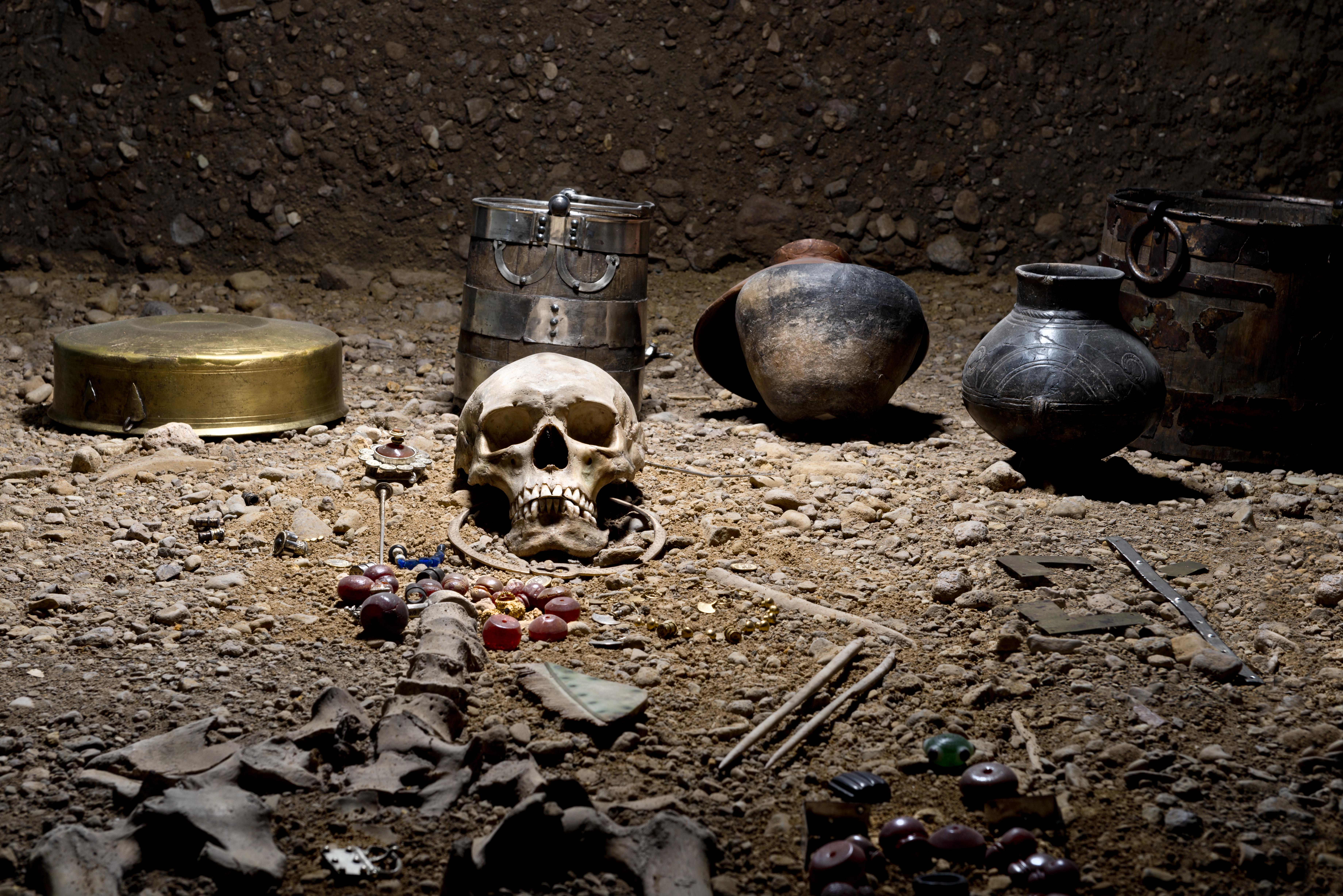 Skelett in Ausstellungsvitrine, umgeben von Gefäßen und Schmuckgegenständen