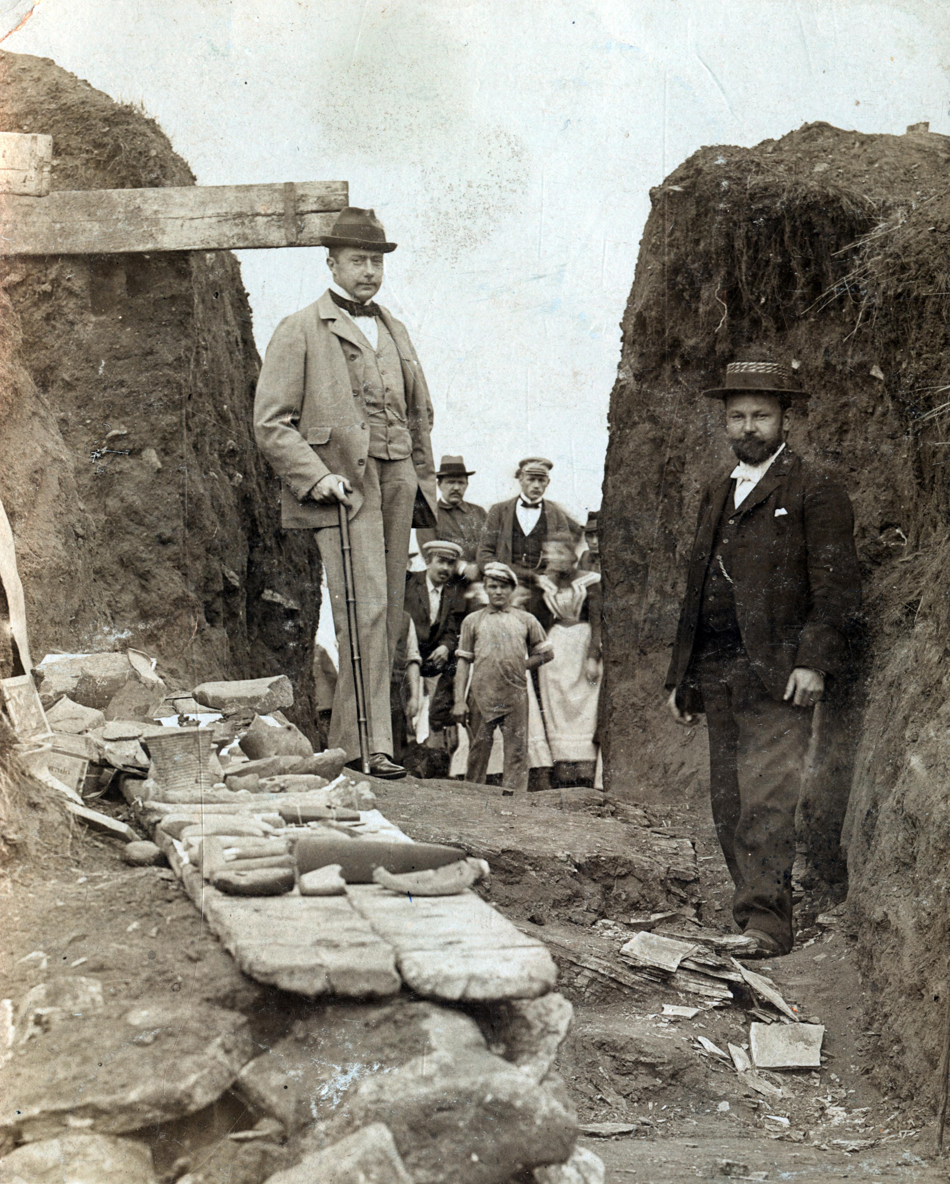 Historisches Foto, zwei Herren neben Funden, vor einem Grabhügel, dazu Zuschauer
