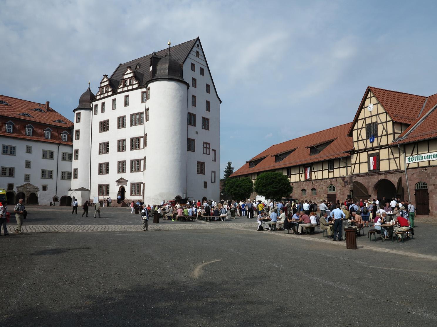 Personen vor dem Schloss Heringen mit strahlend weißer Fassade.