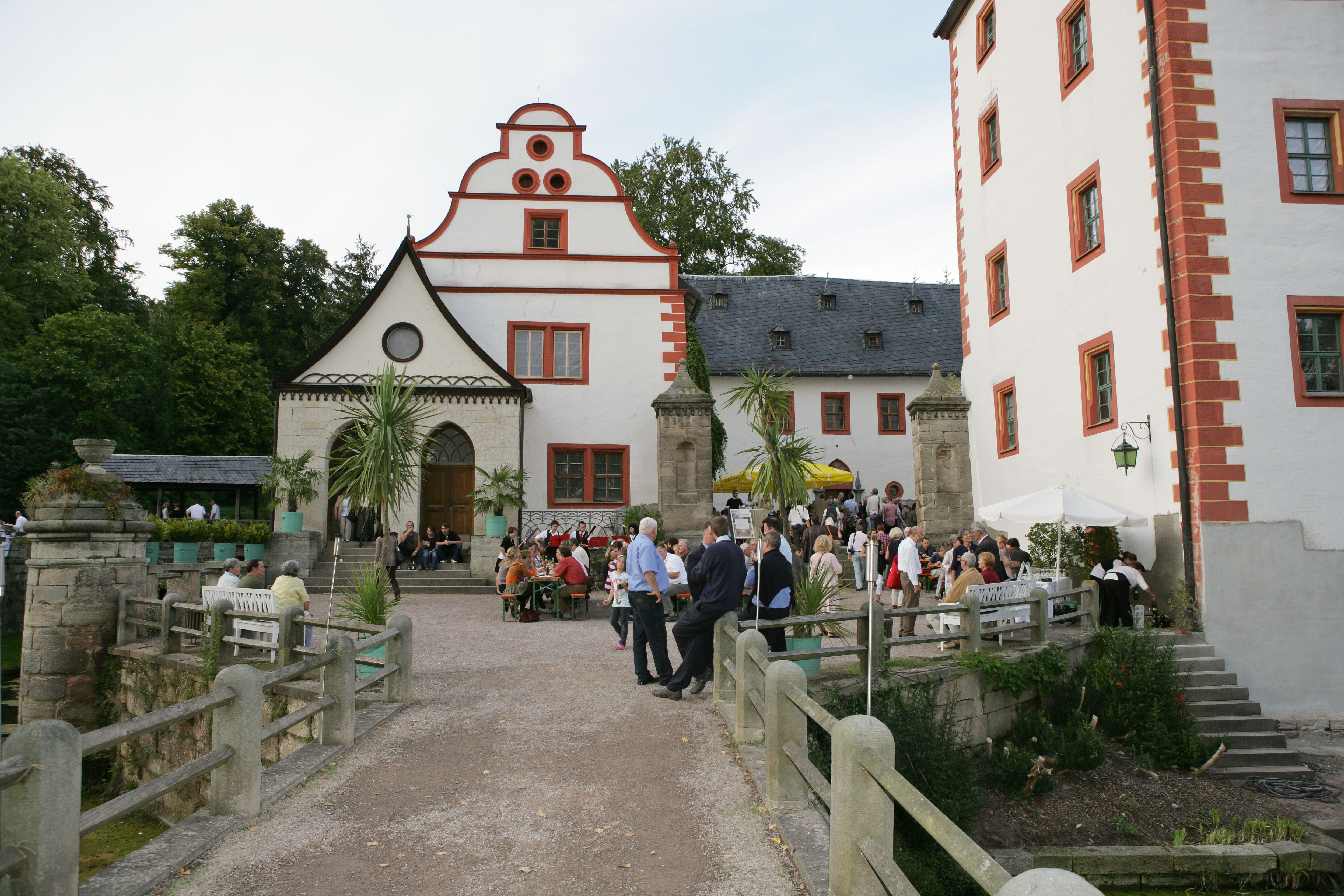 Schlosshof mit sitzenden und stehenden Personen