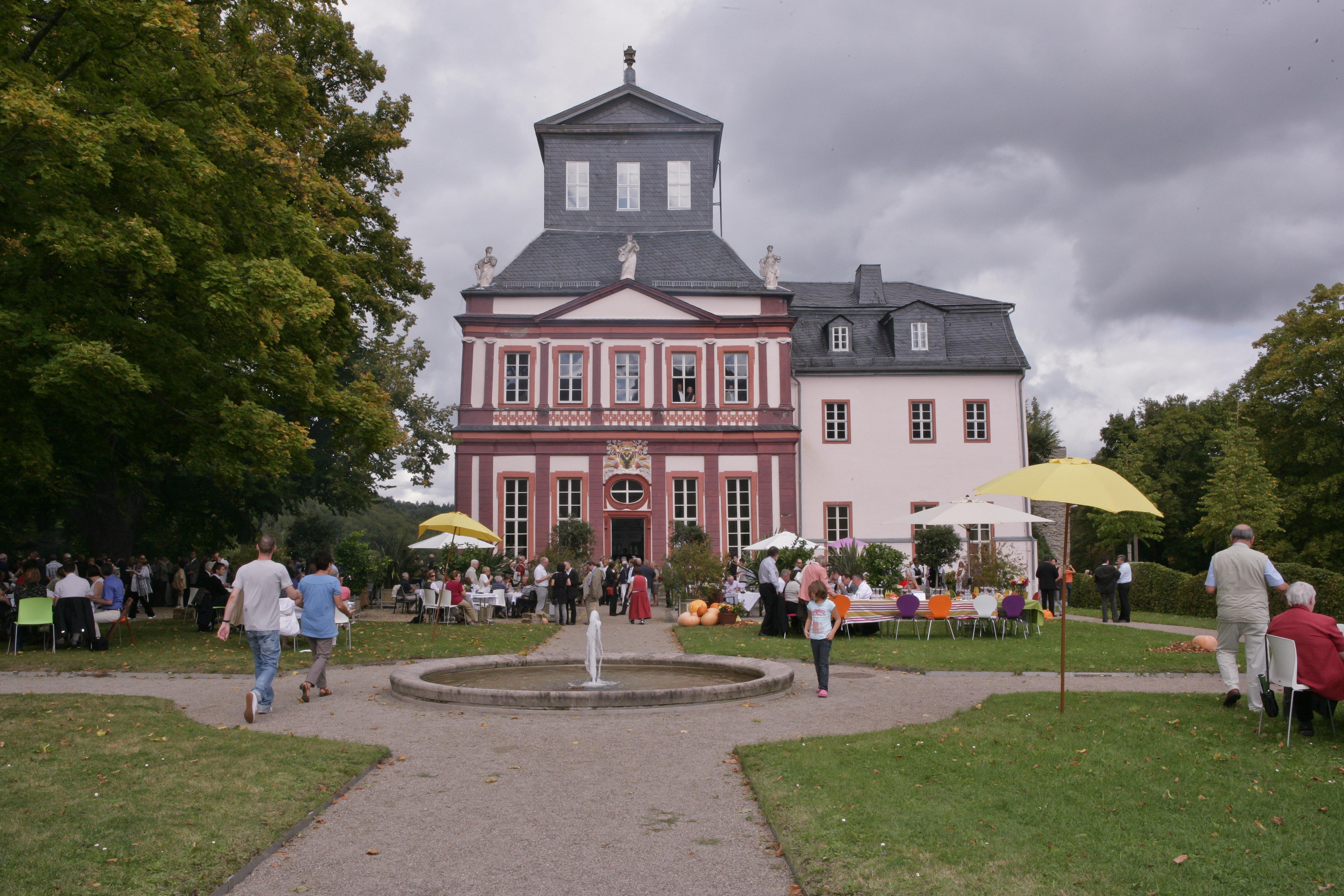 Blick auf Schloss mit Springbrunnen vorne und im Park sitzenden Gästen