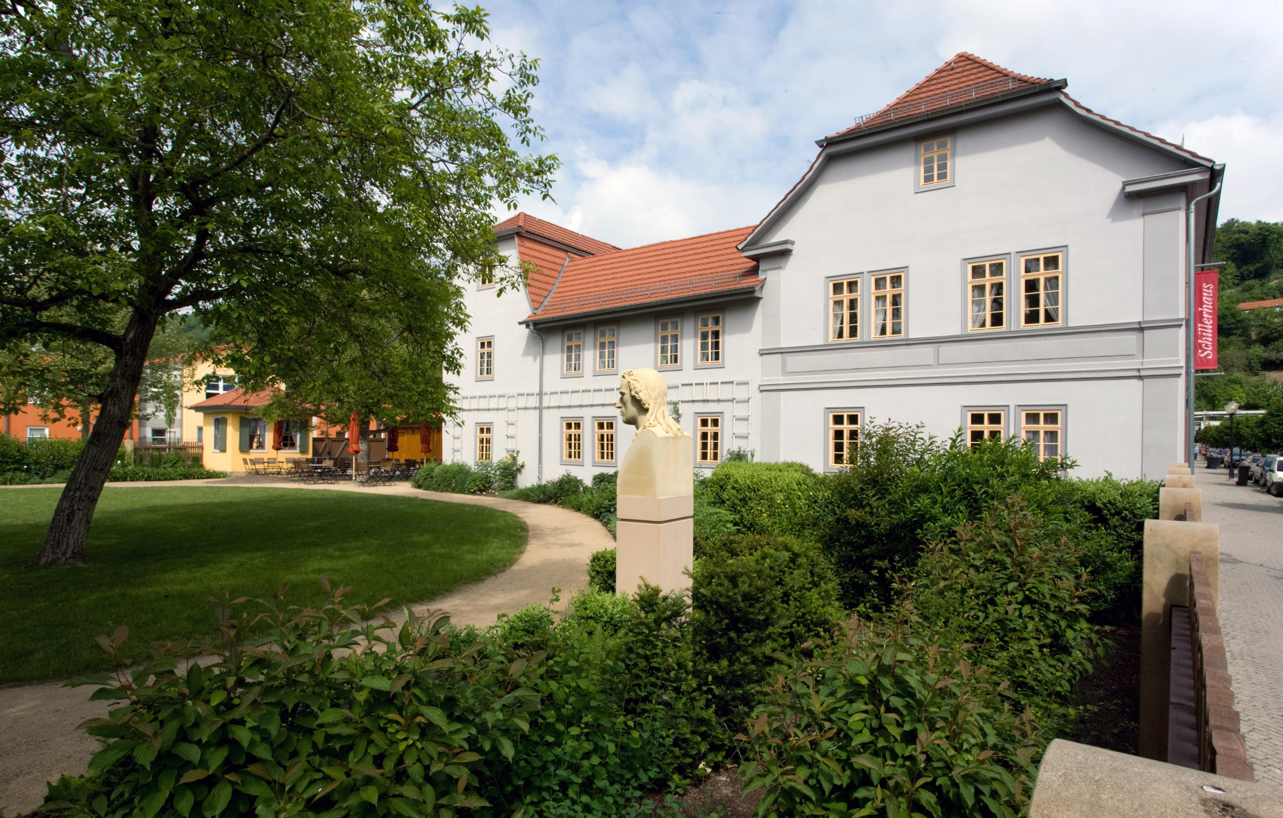 Gartenseitige Ansicht eines blauverputzen zweistöckigem Museumsgebäudesmit Schiller-Büste.