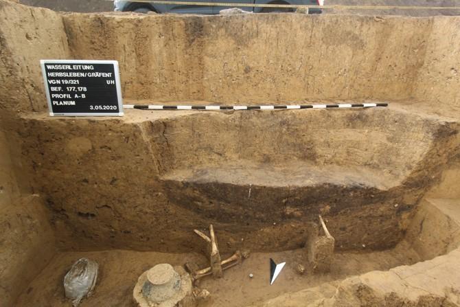 Säuberlich freigelegte Grabgrube, darin Gefäßbeigaben und Skelettknochen
