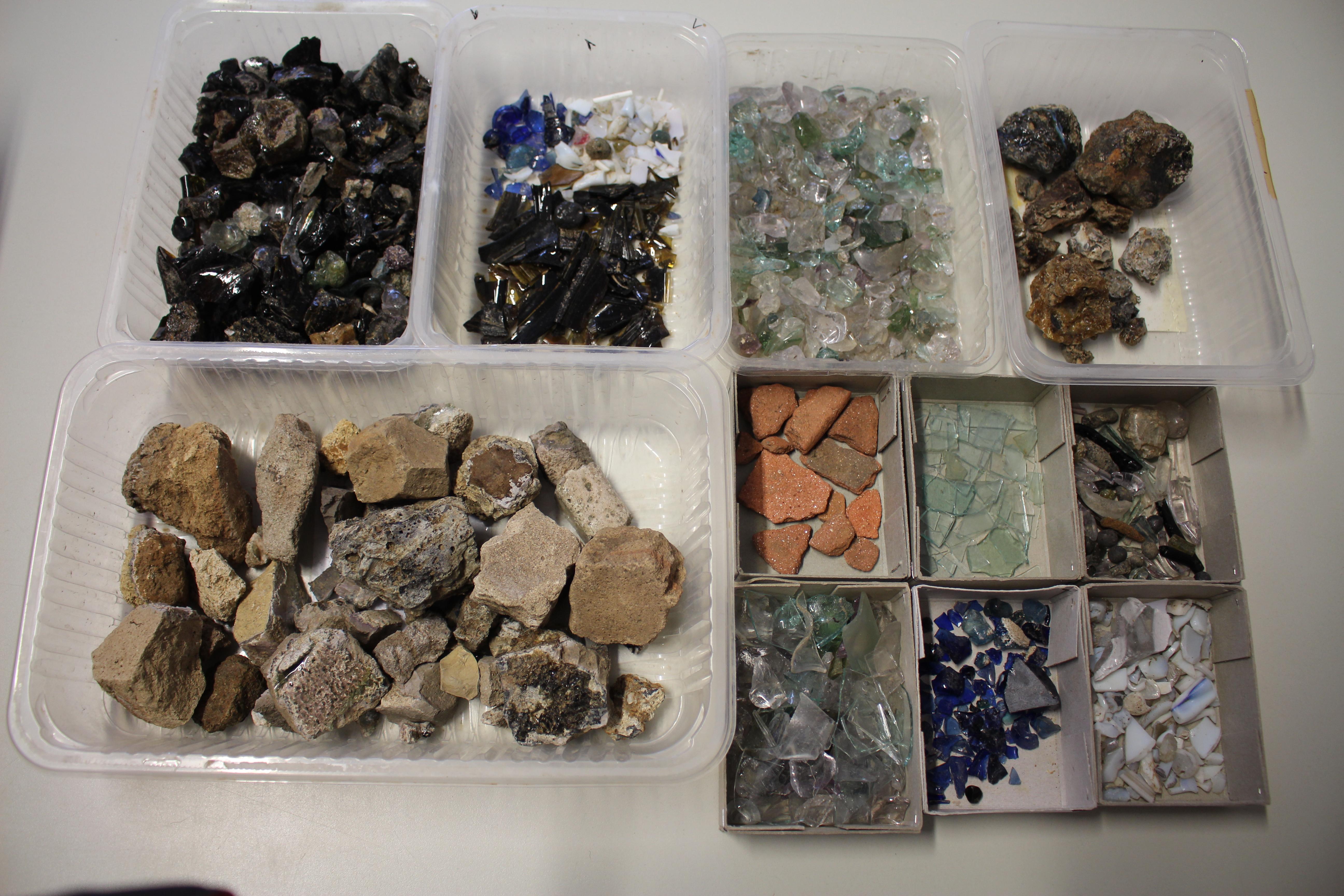 Mehrere Behälter mit verschiedenen, sortierten Überresten der Glashüttenprodukte