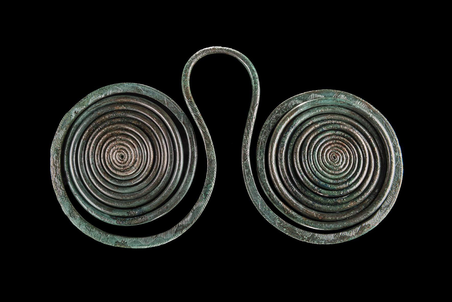 Eine sogenannte Brillenspirale aus rundem Bronzedraht, grün patiniert