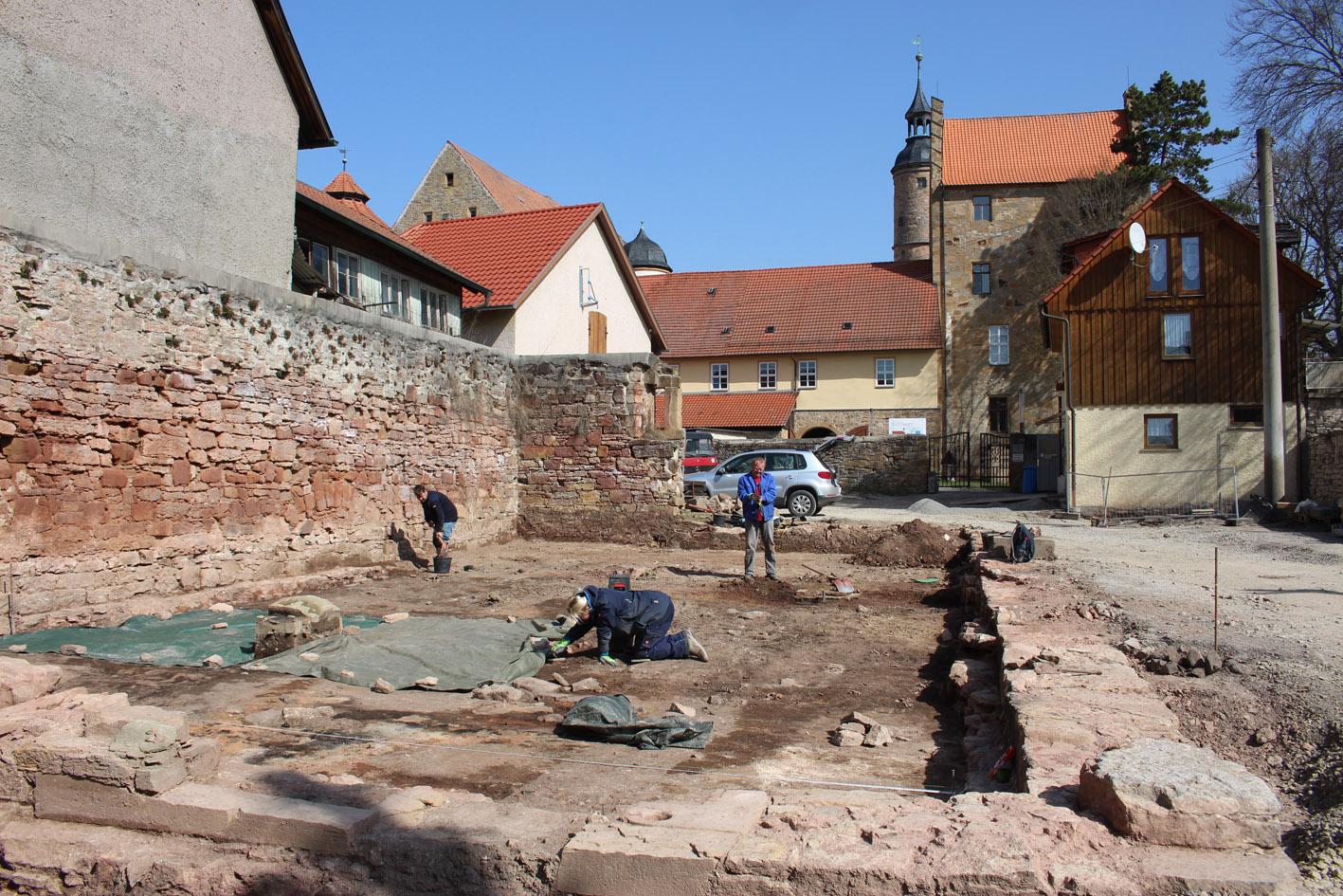 Grabungsfläche, im Vordergrund Grabungsmitarbeiter, im Hintergrund Schlossturm