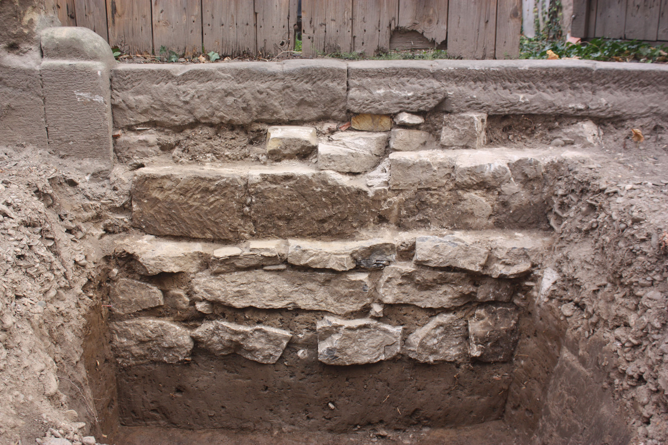Freigelegte Steinmauer mit vier Steinreihen unter heutigem Erdboden erhalten