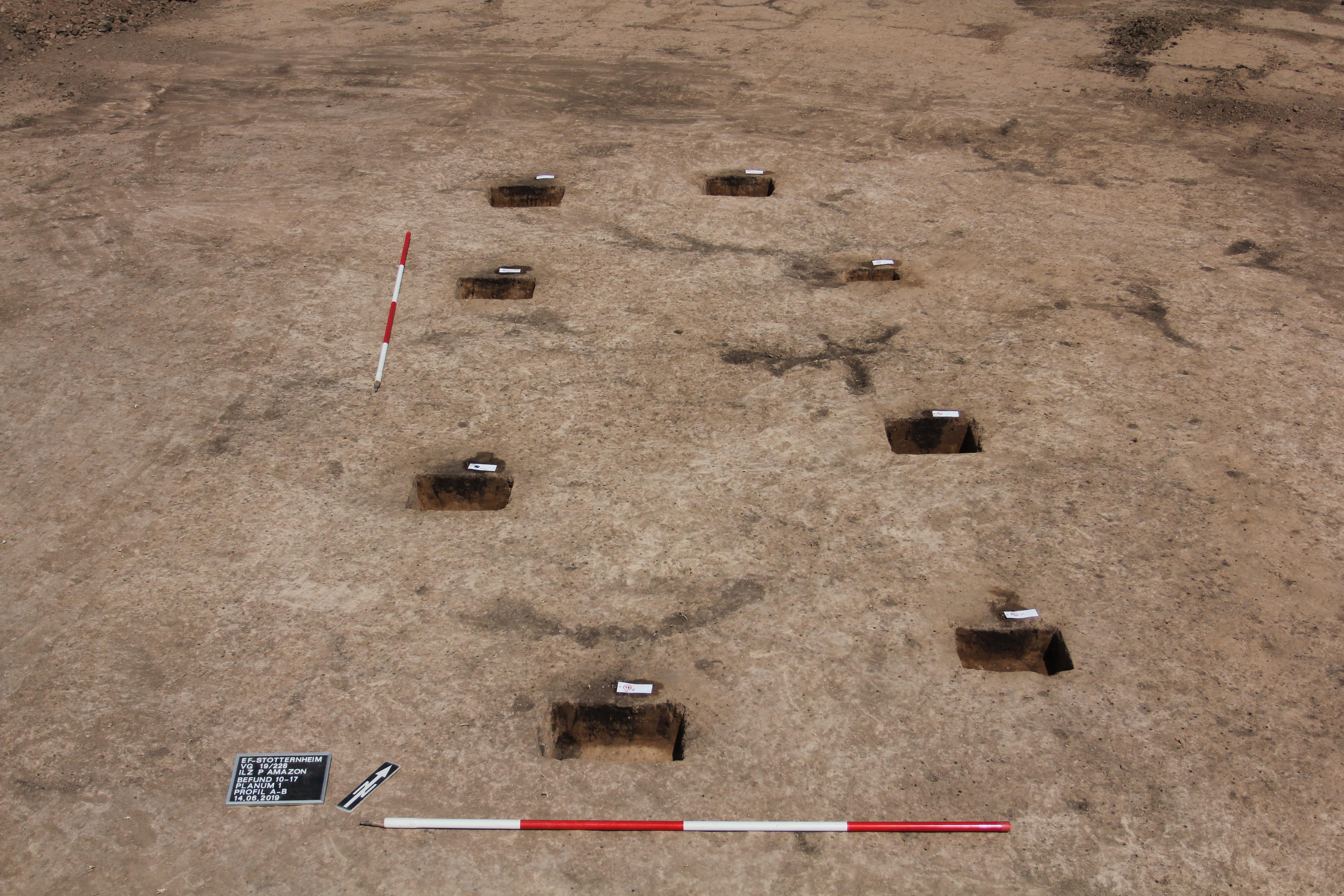 Braunrötlicher Erduntergrund zeigt dunkle Pfostenspuren von Hausgrundriss