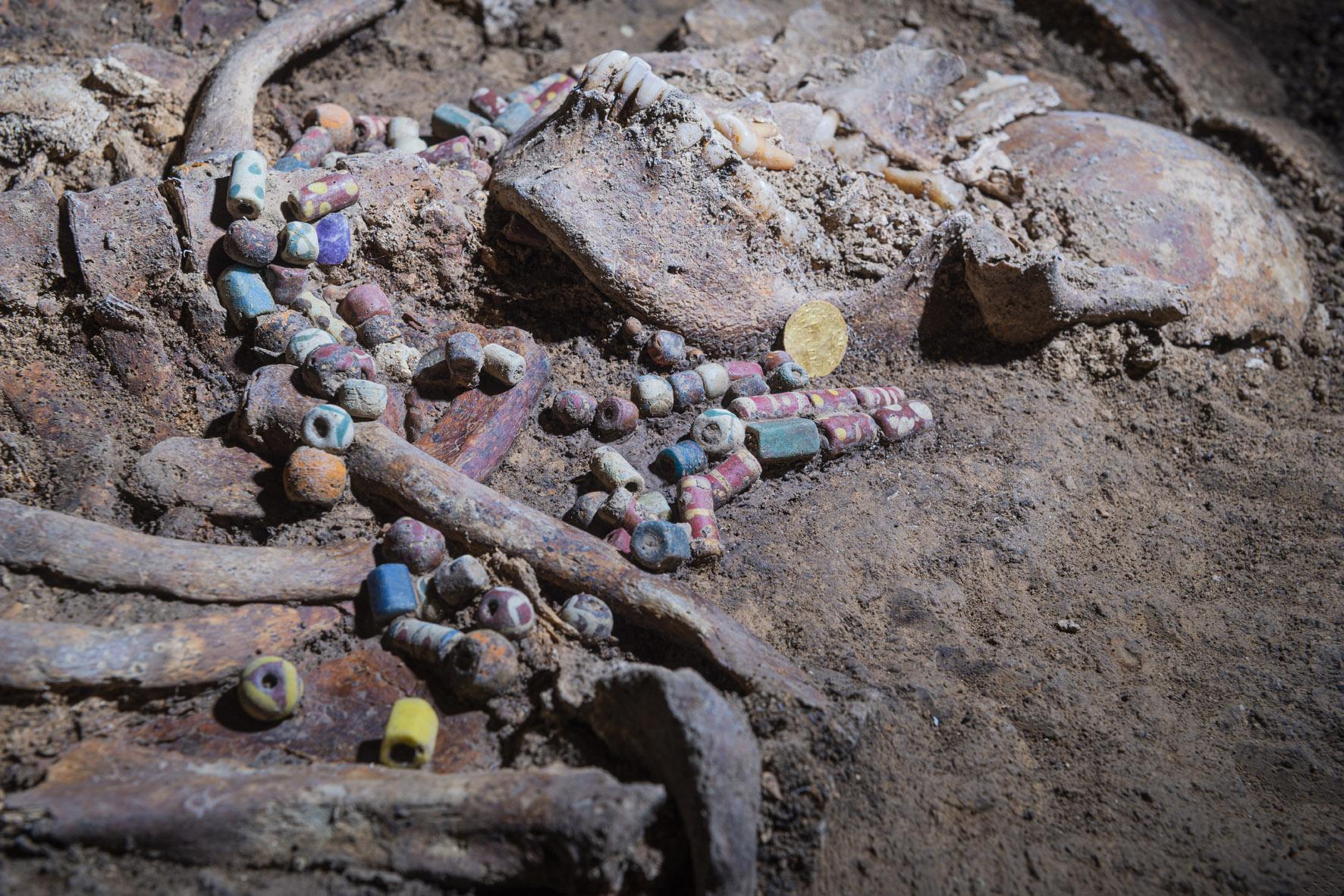Über Halsbereich eines Skelettes liegen bunte Glasperlen, daneben eine Goldmünze