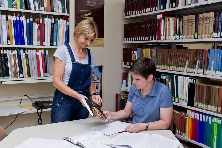 Person an Tisch mit Unterlagen, und bekommt von Bibliothekarin Buch gereicht