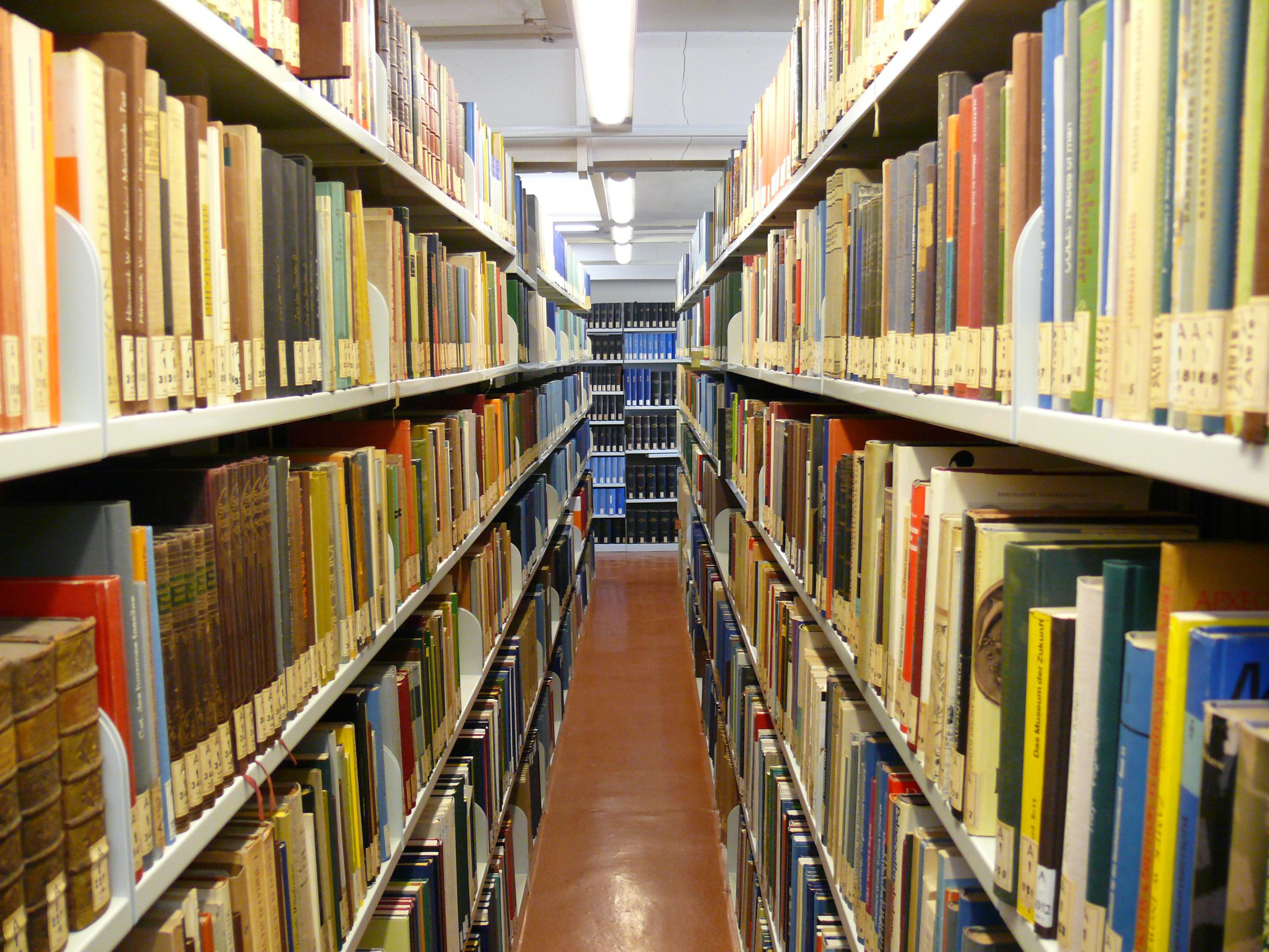 Blick durch zwei mit Büchern vollgestellten Regalreihen in der Bibliothek