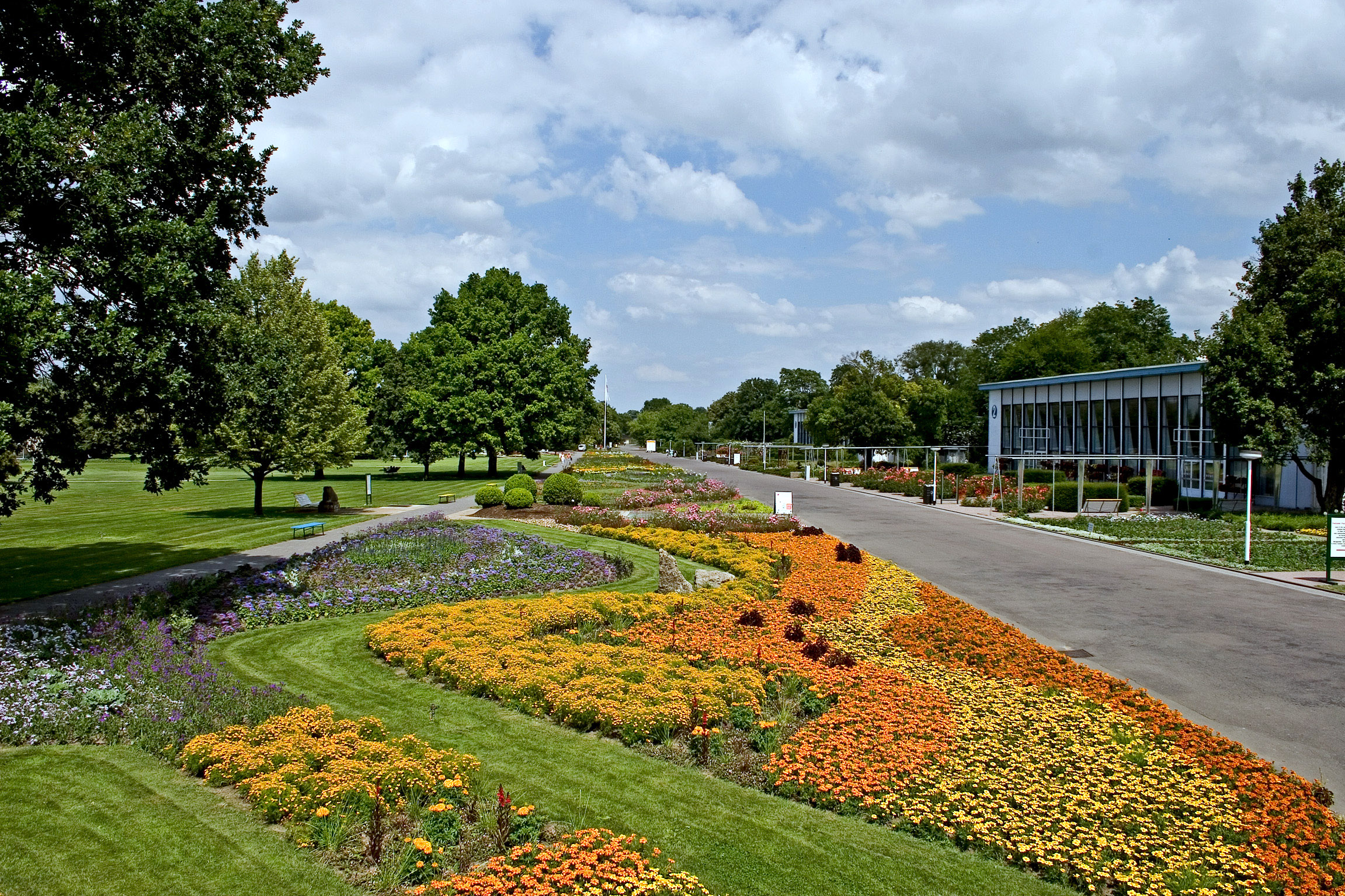 Mittig bunte Blumenrabatte. Rechts Weg mit Blumenhalle. Links Bäume mit Wiese