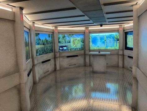 Blick in den Besucherraum mit Bildschirmen als Fenster
