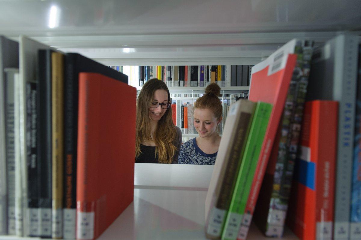 Blick durch eine Buchlücke im Bücherregal auf zwei junge Frauen, die lächelnd nach unten schauen, vermutlich in ein Buch hinein
