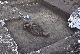 Foto: Blick auf ein freigelegtes Skelett im Boden, daneben größere dunkle Erdverfärbung als Befund