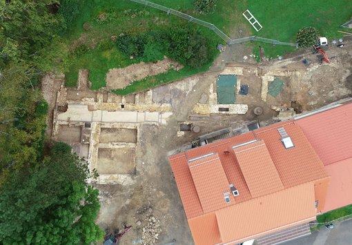 Luftbild, neben Haus sind auf Grabungsfläche alte Mauerfundamente freigelegt