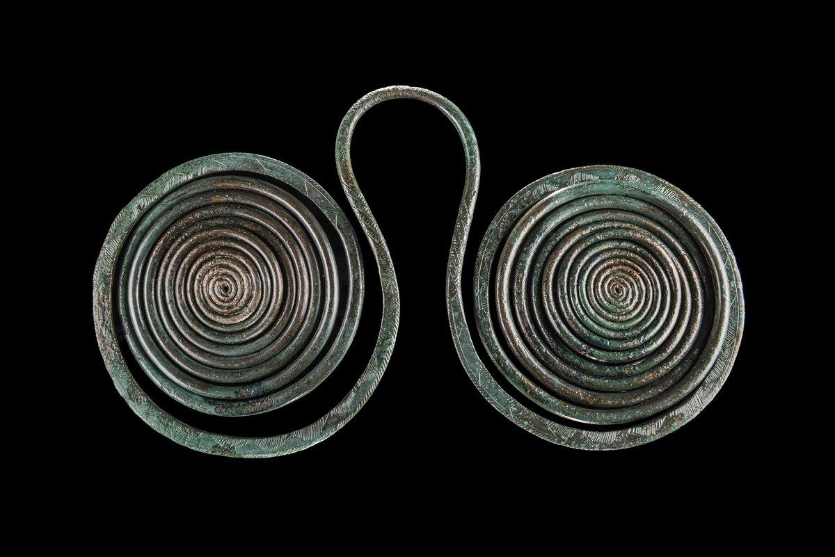 Eine sogenannte Brillenspirale der mittleren Bronzezeit, gefertigt aus rundem Bronzedraht: Ein Bügel in der Mitte verbindet zwei gegenläufig eingerollte, flache Spiralen, die Bronze ist dunkelgrün angelaufen, schwarzer Bildhintergrund