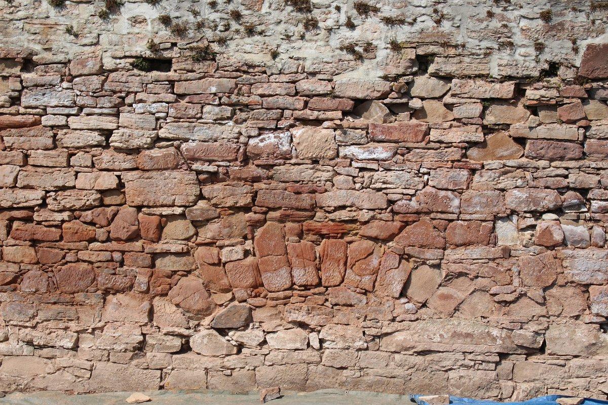 Inmitten einer Steinmauer aus rötlichen, waagrecht gesetzten Steinreihen hebt sich die nach oben gewölbte runde Mauerung eines Entlastungsbogens ab
