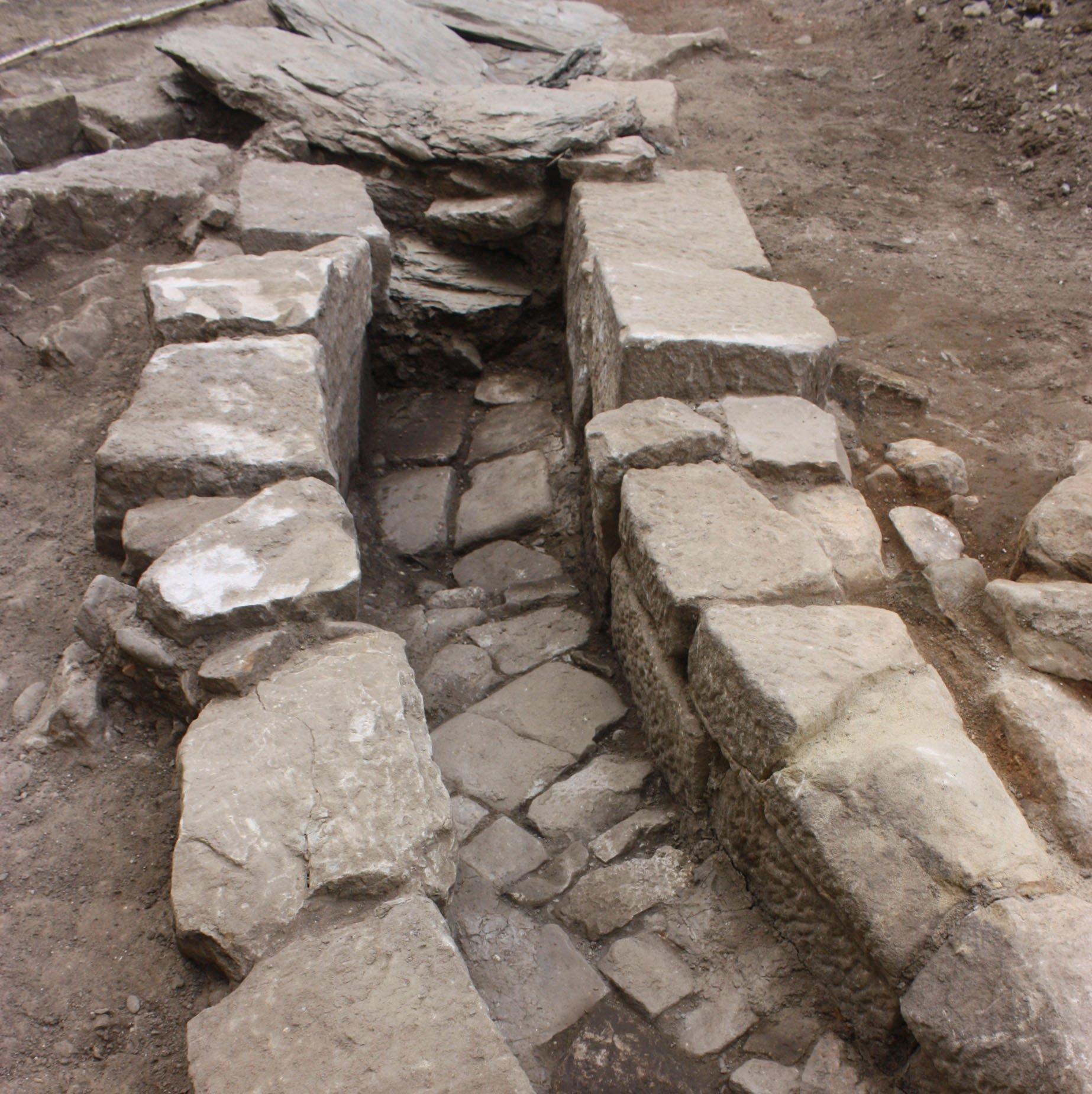 Kanal aus aufgeschichteten, großen eckigen Steinen und Steinboden