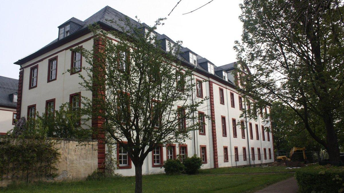 Rechteckiges weißes Gebäude mit vier Geschossen, davor Baum