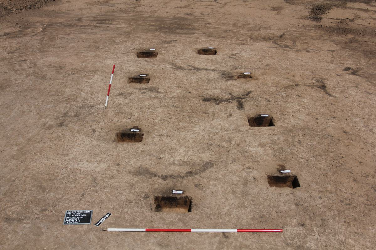 Blick auf ein Grabungsplanum: Auf braunrötlichem Erduntergrund treten dunkle Pfostenspuren eines länglichen Hausgrundrisses deutlich hervor; Messstangen, ein Nordpfeil und eine Fototafel liegen neben den Befunden